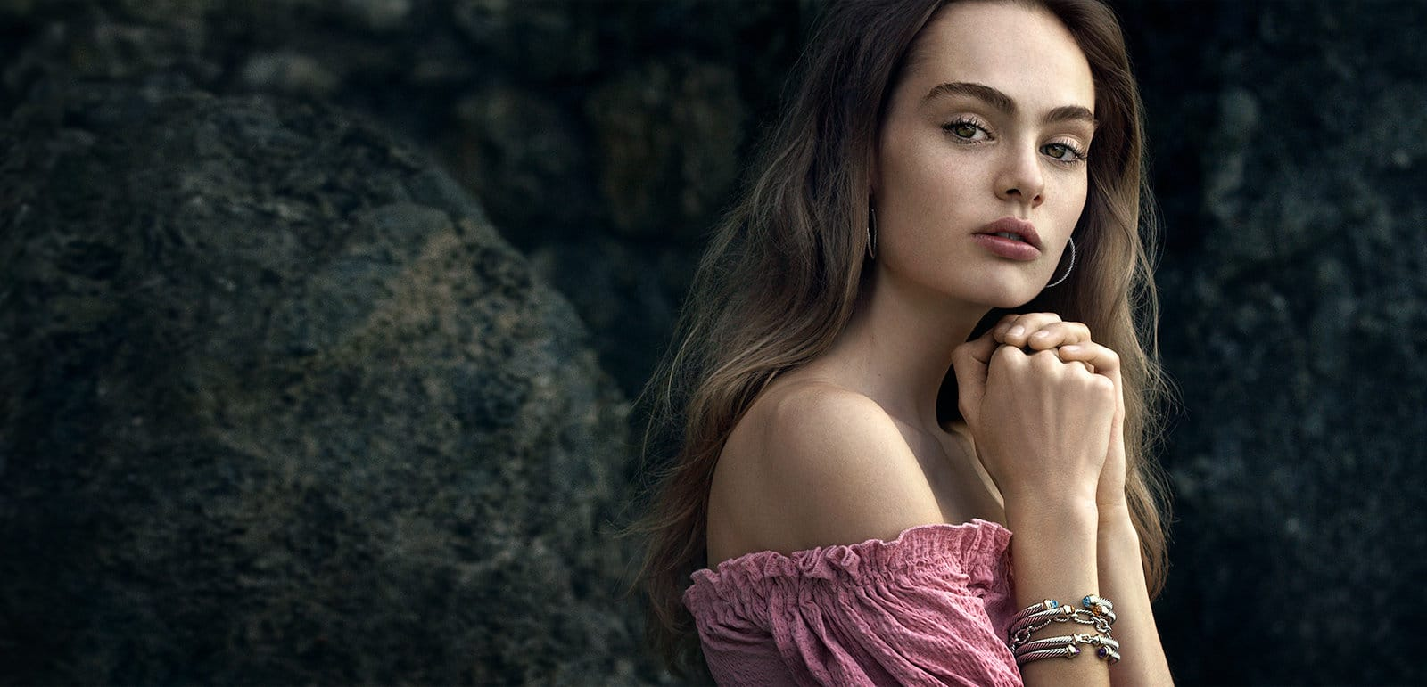A color photo of model Florence Clapcott standing in front of dark rocks while wearing a pink off-the-shoulder top, David Yurman sterling-silver hoop earrings, and a stack of David Yurman link-chain and Cable bracelets in sterling silver with 18K yellow gold accents and colored gemstones.