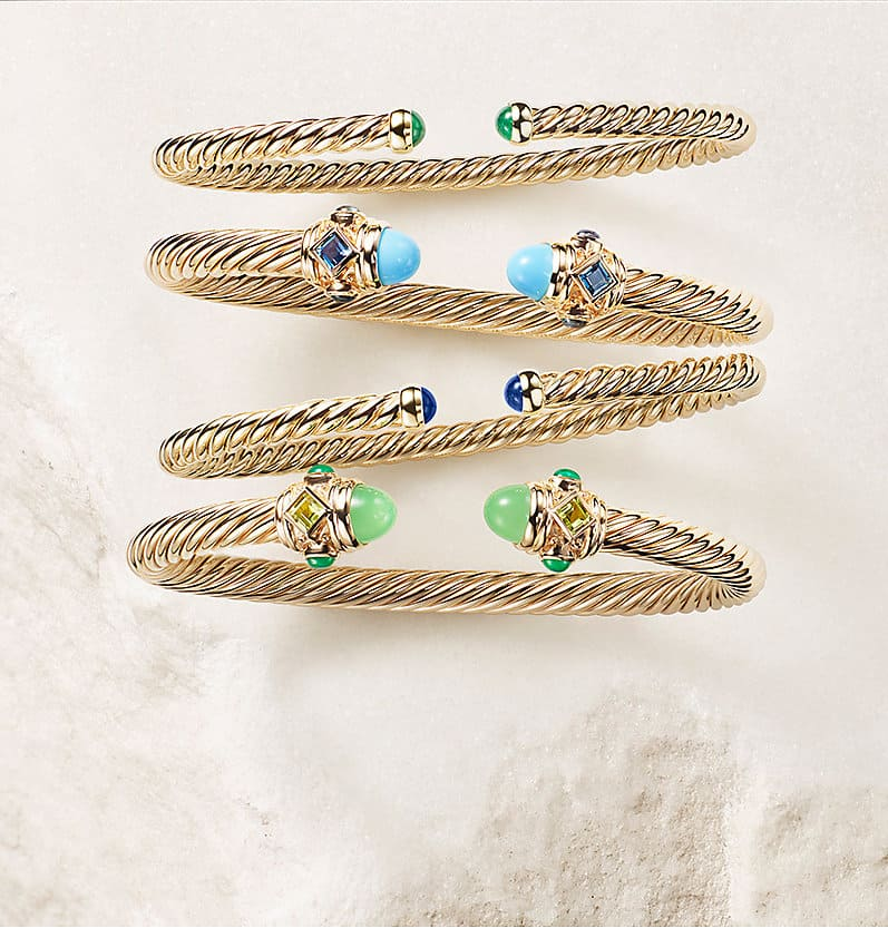 Cablespira® and DY Renaissance® cuffs in 18K yellow gold with or without blue- or green-toned gemstone accents arranged on a white stone.