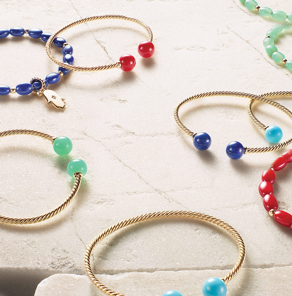 Solari bracelets in 18K yellow gold with chrysoprase, dyed red sea bamboo, lapis lazuli and turquoise, and Spiritual Beads bracelets in 18K yellow gold with chrysoprase, dyed red sea bamboo and lapis lazuli with a gold Hamsa charm, on a stone.