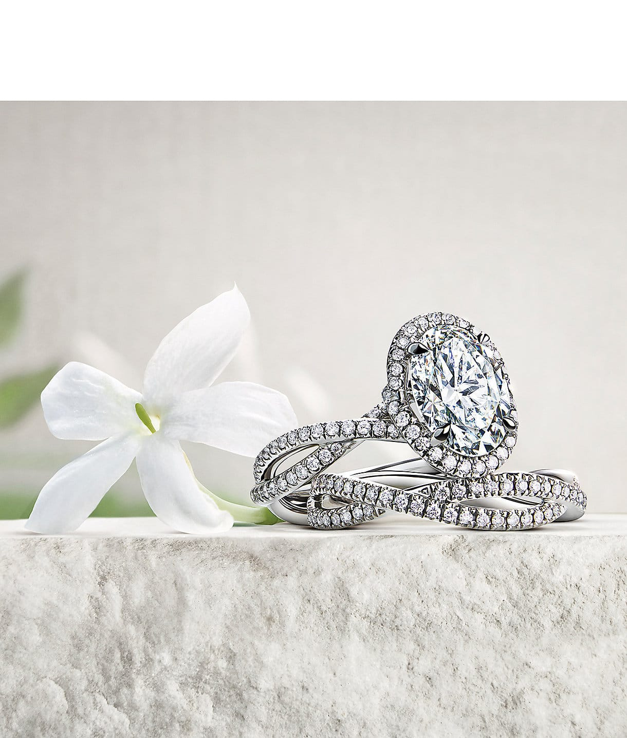 DY Lanai engagement ring and band in platinum with diamonds on a stone with a jasmine flower.