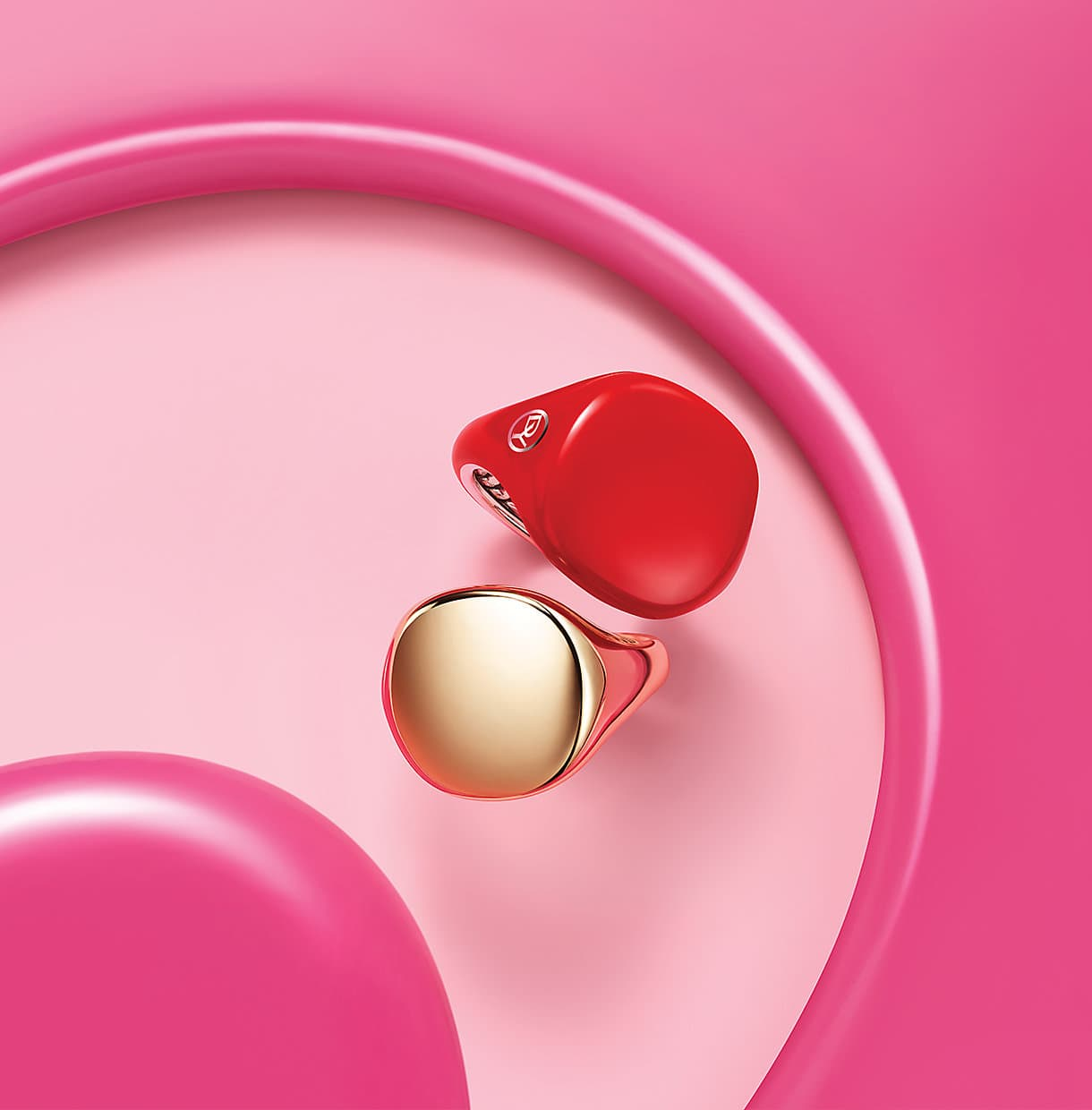 Pinky Rings in sterling silver with red enamel and 18K yellow gold arranged between pools of bright pink paint.