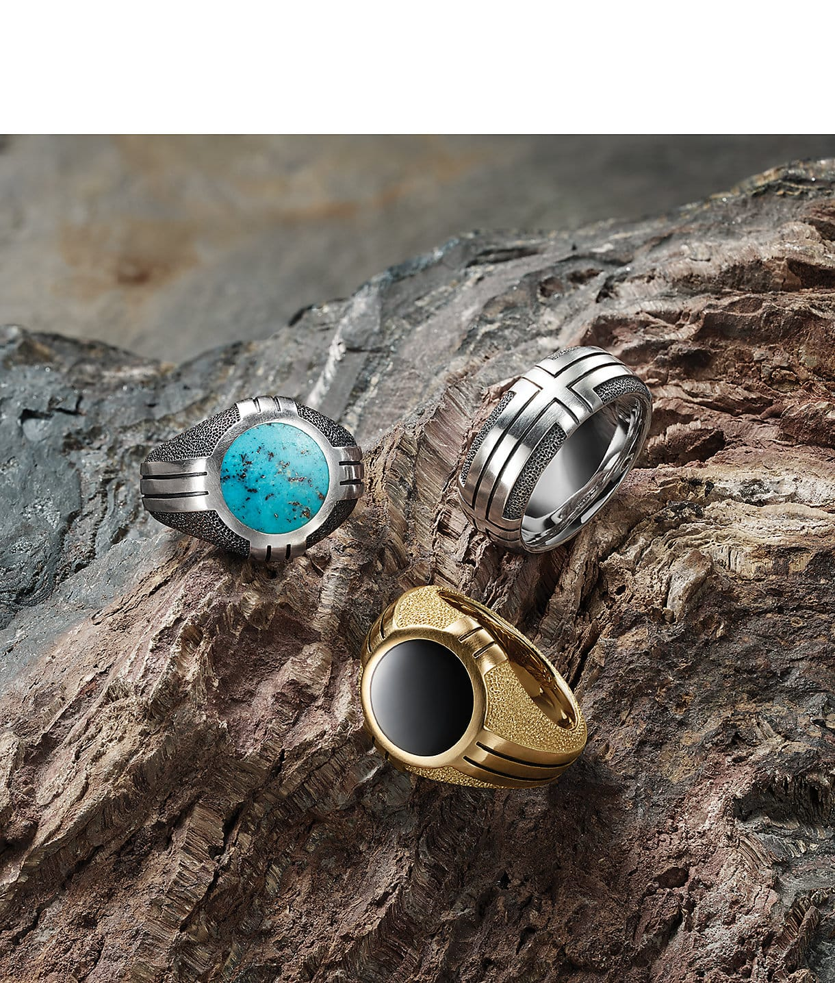 Southwest signet rings in sterling silver with turquoise, gold with black onyx and a Southwest band in sterling silver arranged on the ridges of a multicolored stone.
