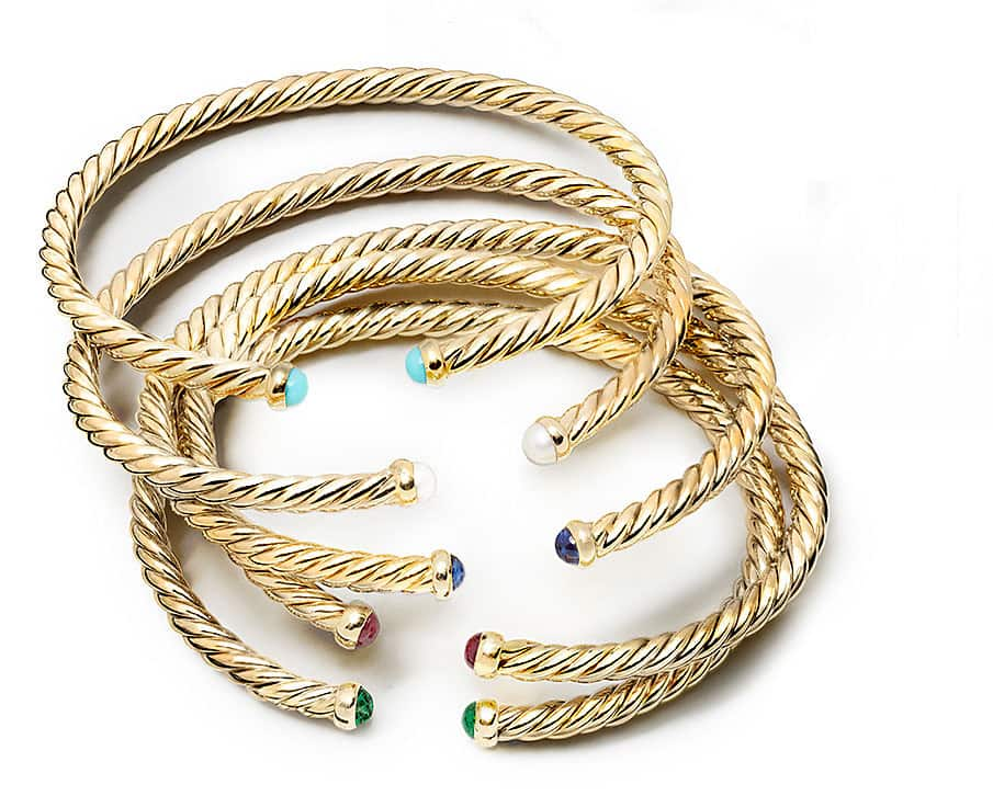 A stack of 18k yellow gold Cable Spira bracelets with colorful gemstone accents