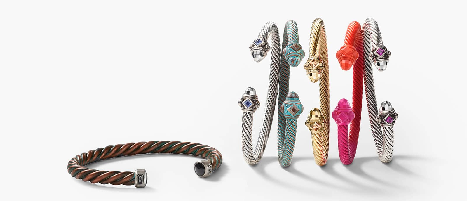 A color photograph of David Yurman men's Cable bracelet lying on the ground next to a horizontal stack of women's Renaissance Collection bracelets in reddish-brown copper, sterling silver, greenish copper, gold or orange-pink aluminum with colored gemstones.