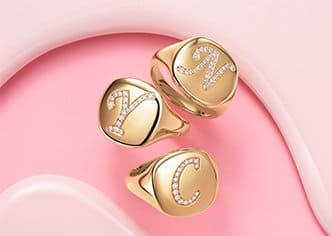 """David Yurman Pinky Rings in 18K yellow gold with pavé diamond """"NYC"""" initials against a colorful backdrop."""