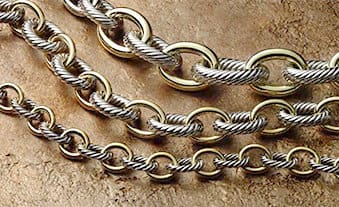 David Yurman chain necklaces in sterling silver Cable links and smooth gold links against a stone backdrop.