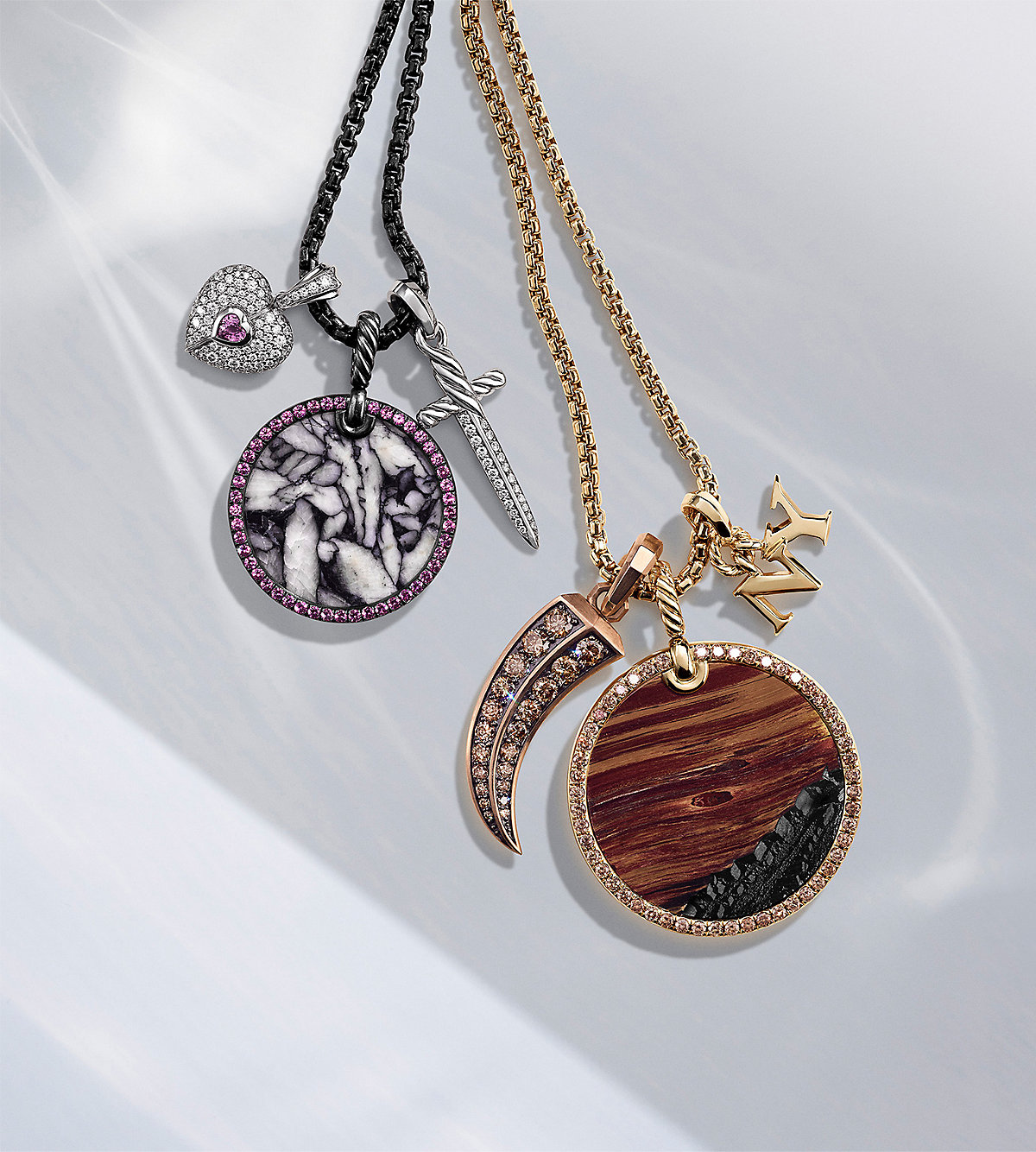 "A color photograph shows two David Yurman chain necklaces strung with three amulet pendants each. The women's jewelry is crafted from 18K yellow, rose or white gold or darkened sterling silver with or without pavé white or cognac diamonds, pink or yellow sapphires, rubies, pinolith or Marra Mamba tiger's eye. The pendants come in various shapes such as a heart, dagger, claw, ""NY"" initials or circles. The jewelry is lying on a white background with soft shadows and reflections."