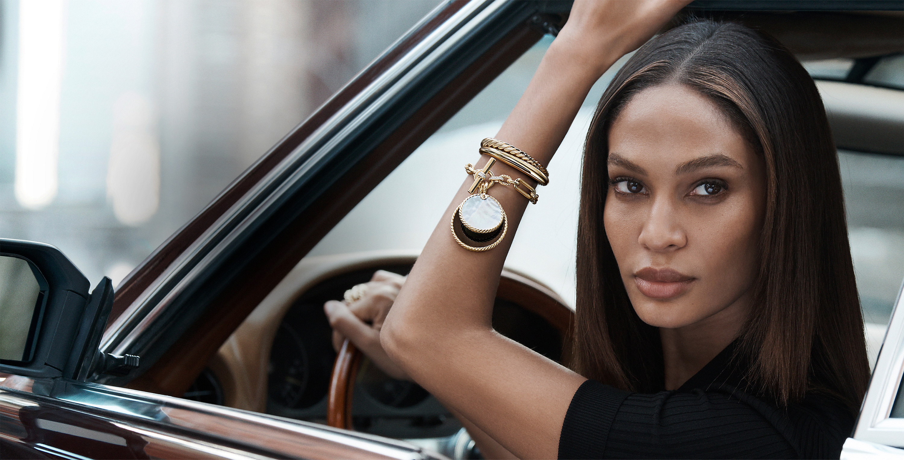 A color photo shows model Joan Smalls from the shoulder up sitting in a car with one arm raised in the window. She's wearing a black top and several David Yurman bracelets with Elements enhancers stacked on one wrist. The jewelry is crafted from 18K yellow gold with or without pavé diamonds, mother-of-pearl or black onyx.
