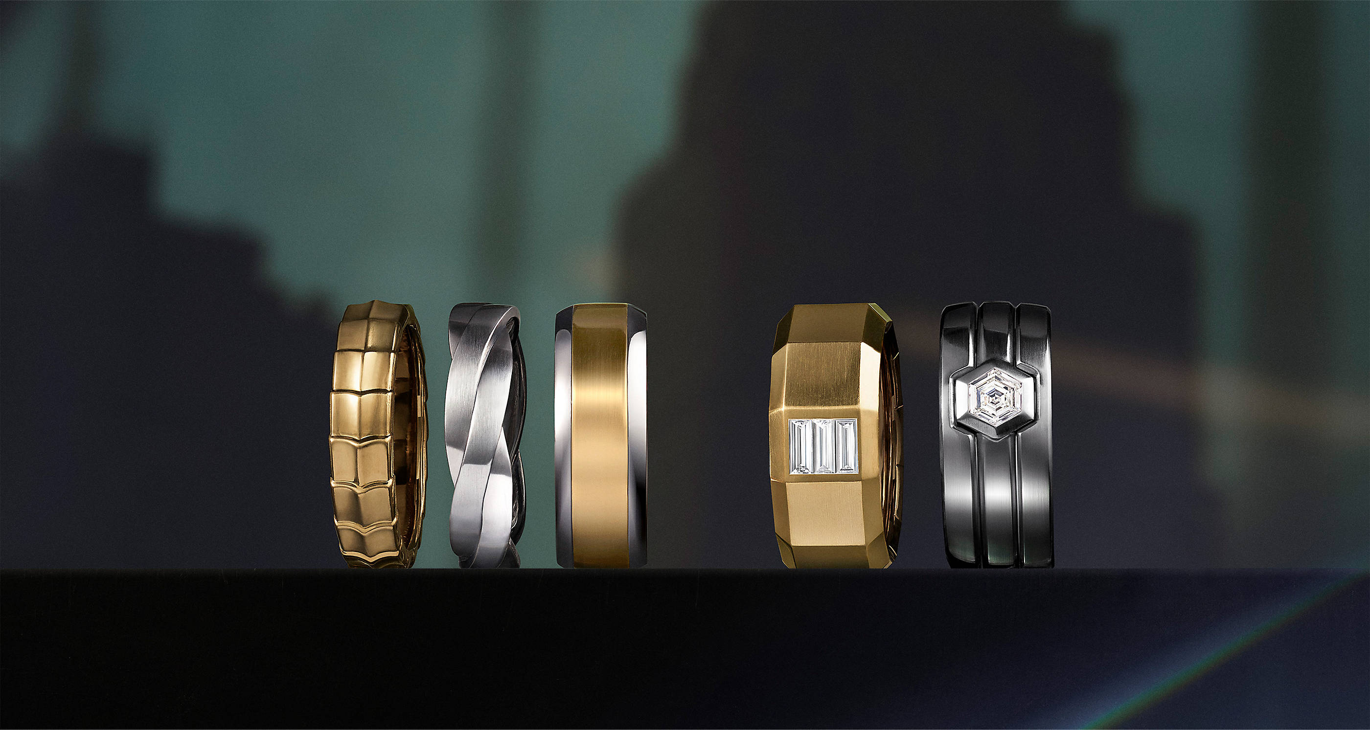 A color photo shows a horizontal row of five David Yurman men's bands standing on a dark reflective surface with a projection of a city building in the background. The bands are crafted from 18K yellow gold, sterling silver, mixed metals, or 18K yellow gold or platinum with center white diamonds.