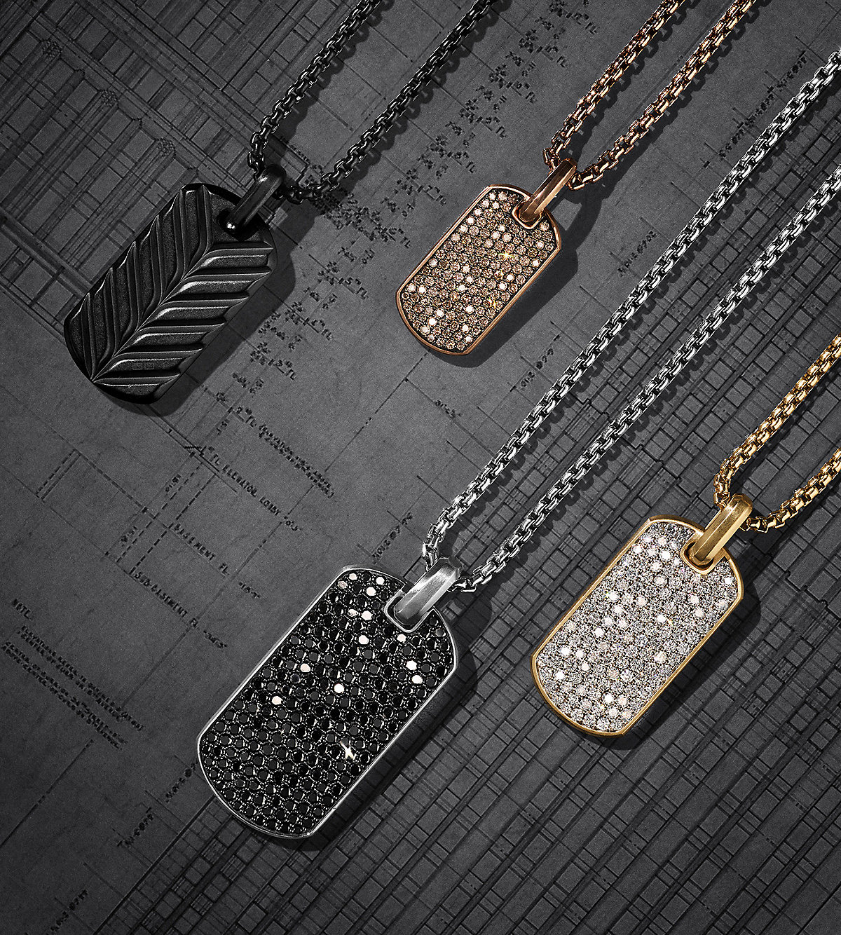 A color photo shows four tags and box chains lying diagonally on a dark grey architectural rendering in a diagonal row. The jewelry is crafted of black titanium, blackened stainless steel, 18K rose or yellow gold, or sterling silver with or without cognac, black or white diamonds.