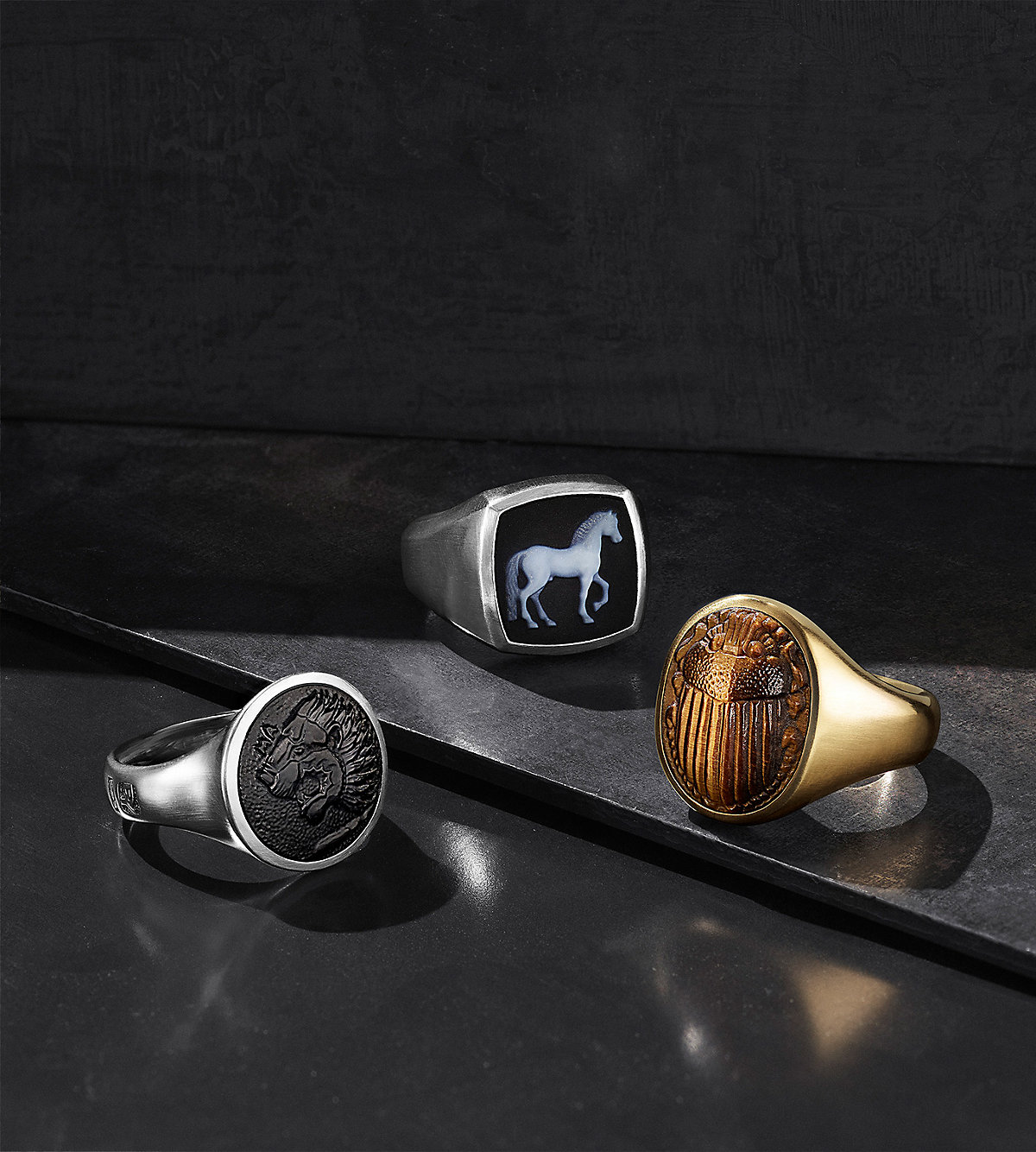 A color photo shows three David Yurman men's Petrvs signet rings scattered on a dark grey stepped stone surface. The rings each feature a carved center gemstone with a lion, horse or scarab in black onyx, banded agate or tiger's eye. The jewelry is crafted from sterling silver or 18K yellow gold.