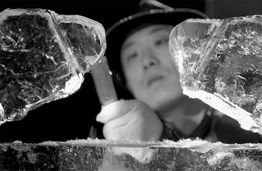 A black-and-white photo of Shintaro Okamoto wearing white gloves while carving a DY cable bracelet from ice.