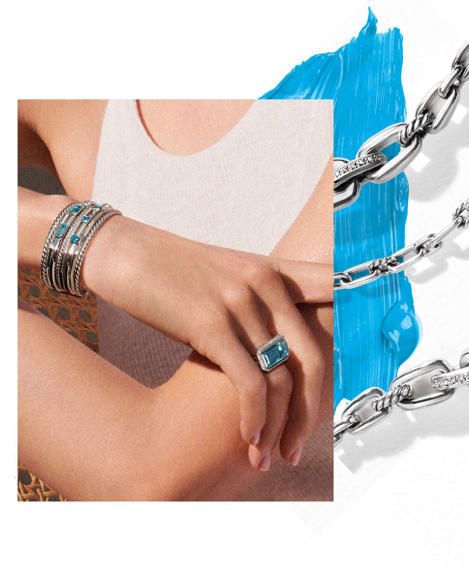 A color photo shows a close-up of a woman's right hand crossed over her left forearm in front of the white tank top she's wearing. The detail of a brown wicker chair she is sitting in is visible between her crossed arms. On her right arm she is wearing a David Yurman multi-row Stax bracelet and a David Yurman statement Novella ring. The jewelry is crafted from sterling silver with blue topaz and pavé white diamonds. Coming out from under the right side of the photo are three sections of a David Yurman Wellesley Link necklace casting long shadows. The jewelry is crafted from sterling silver with pavé white diamonds. Under the upper-right corner of photo and beneath the parts of the Wellesley Link necklace is a heavy streak of cerulean-blue paint.