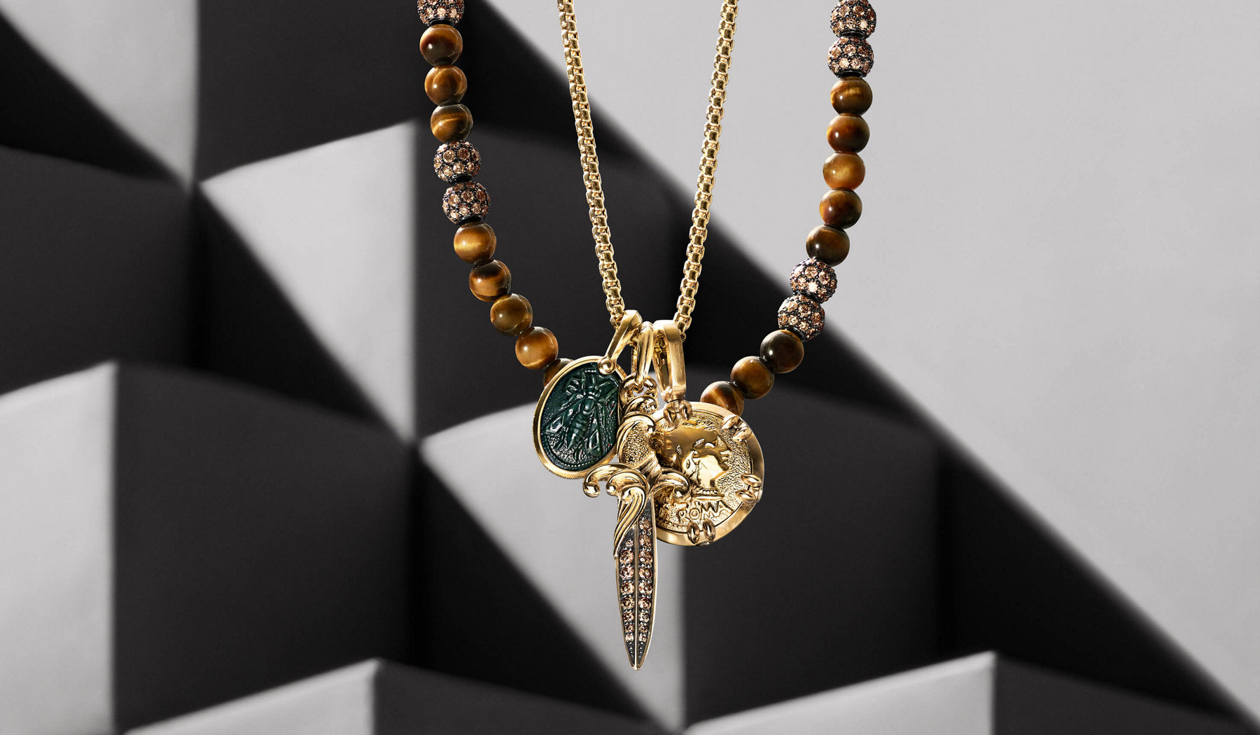 A color photograph shows a David Yurman men's Chain necklace strung with three amulets hanging in front of a Spiritual Beads necklace, with both of the necklaces hanging in front of an out-of-focus tower of cube-shaped beige stone blocks covered in diagonal shadows and rays of light. The chain necklace is crafted from 18K yellow gold, and the three amulets, from left, include a Petrvs bee amulet in 18K yellow gold with bloodstone, a Waves dagger amulet in 18K yellow gold with pavé cognac diamonds and a Roman coin amulet in 18K yellow gold. The bead necklace is crafted from tiger's eye with sterling silver and pavé cognac diamonds.