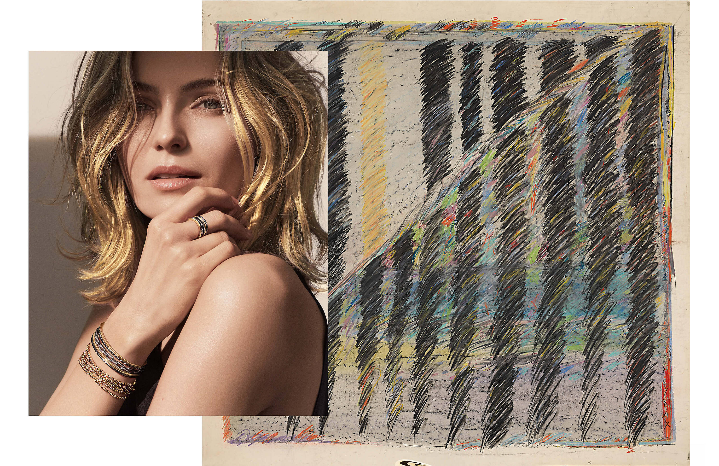 "A color photograph showing a woman wearing David Yurman jewelry is overlaid over the left side of an abstract, colorful scribble painting. The woman is seen in the light with shadows across her forehead and behind her, and has her hair parted to frame her face and her right arm crossed so her right hand is resting on her left shoulder. She is wearing a Stax multi-row ring, a Stax multi-row bracelet, and a Chain necklace as a bracelet. The jewelry is crafted from 18K yellow gold or from blackened sterling silver with 18K yellow gold and pavé white diamonds. Under the corner of the painting is a caption that reads ""Untitled, mixed media, Sybil Yurman."""