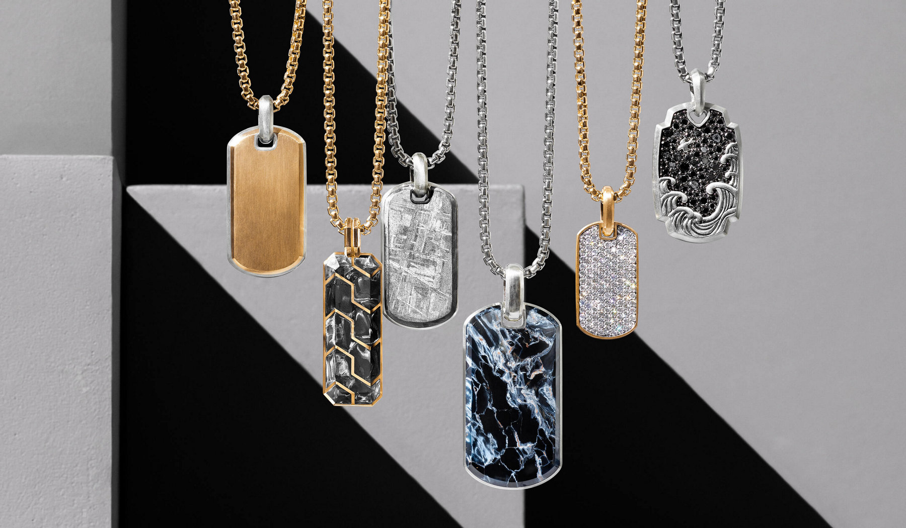 A color photograph shows six David Yurman men's tags hanging at alternating levels in a horizontal row, with each strung on an individual David Yurman men's Chain necklace crafted from sterling silver or 18K yellow gold. The jewelry is hanging in front of a beige stone block and beige stone background, both of which are covered half by a diagonal ray of light and the other half in shadow. From left, the tags include a Streamline design in sterling silver with 18K yellow gold, a Foged Carbon ingot design in 18K yellow gold, a Meteorite design in sterling silver, a Streamline design in sterling silver with pietersite, a Streamline design in 18K yellow gold with pavé white diamonds and a Waves design in sterling silver with pavé black diamonds.