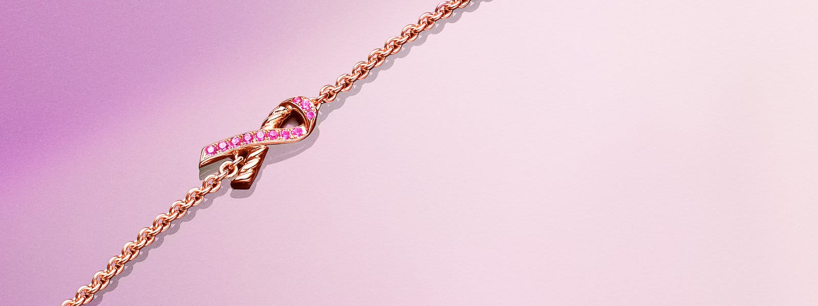 A color photograph shows a David Yurman limited-edition BCRF pink ribbon bracelet on top of a deep pink and purple angular surface with a while line running parallel to the bracelet. The bracelet is crafted from 18K rose gold with pink sapphires.