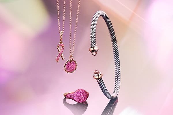 A color photo shows a David Yurman BCRF ribbon pendant necklace and a circular pendant necklace hanging above a pinky ring and next to a sterling silver Cable bracelet. The jewelry is crafted from 18K rose gold with pink gemstones and are all shot against a bright pink background with a silver-colored piece of metal, and reflections of light and jewelry.