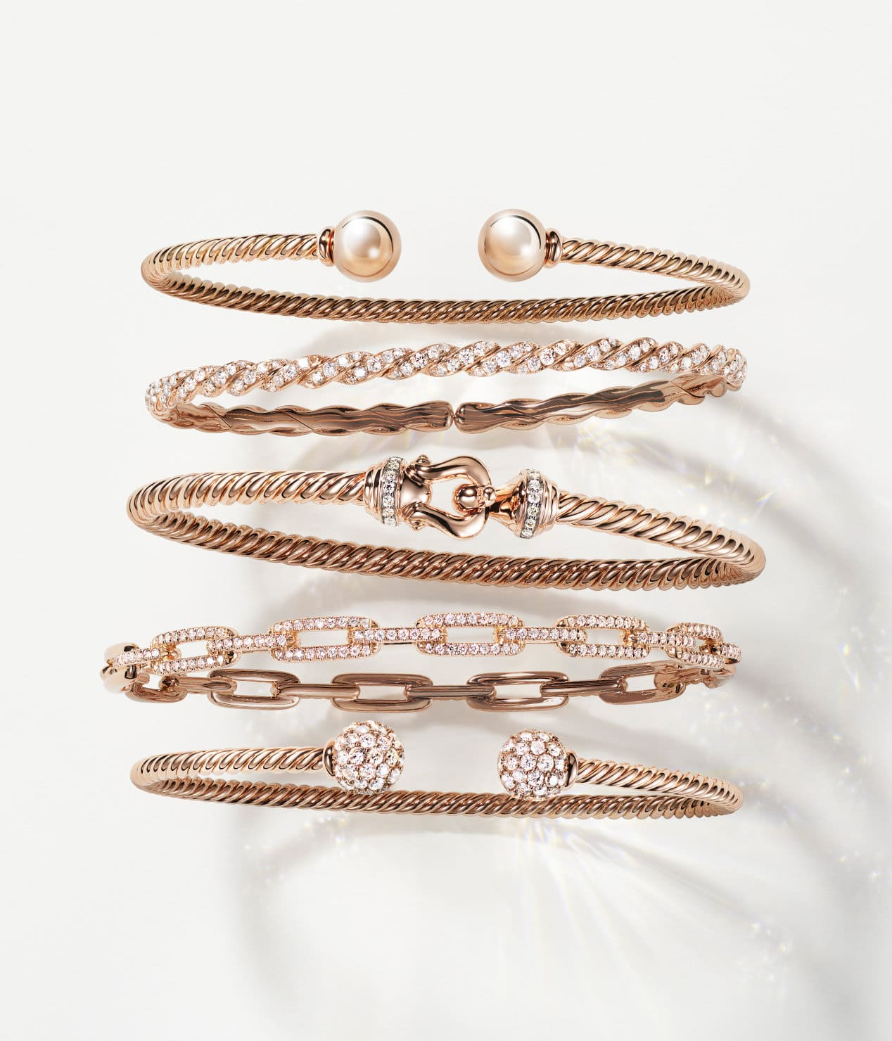 A color photograph shows a vertical row of five David Yurman bracelets on a white background. The women's jewelry is crafted from 18K yellow gold with pavé diamonds. Four of the bracelets feature Cable, a buckle motif or ball-shaped ends, while one bracelet is a chain-link design.