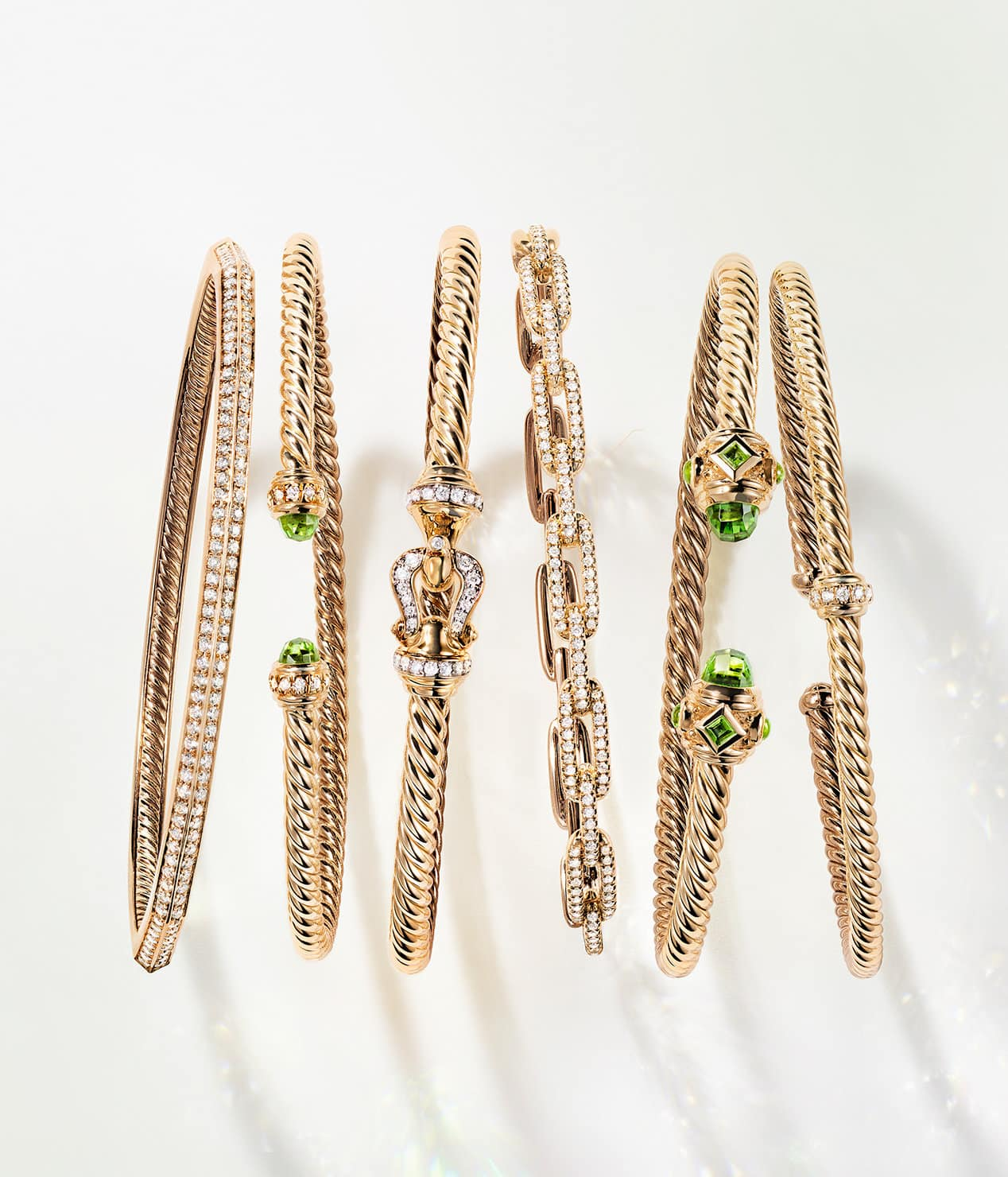A color photograph shows a horizontal row of six David Yurman Cable, chain and faceted bracelets standing on a white background with soft shadows. The women's jewelry is crafted from 18K yellow gold with or without pavé diamonds and peridot accents on the bracelet ends.