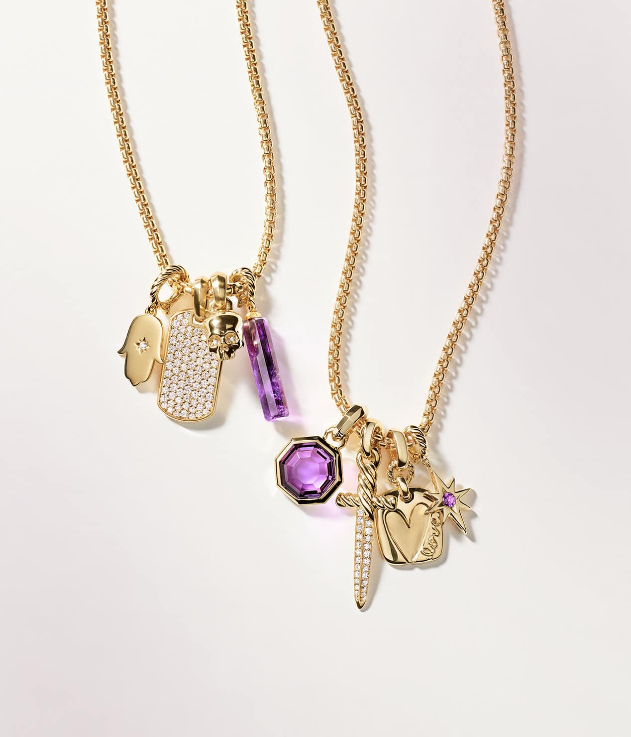 A color photograph shows two David Yurman chain necklaces strung with four amulets each draped on a white background. The women's jewelry is crafted from 18K yellow gold with or without pavé diamonds and amethyst center stones. The amulets come in various shapes such as a Hamsa hand, tag, skull, barrel, octagon, dagger and heart.