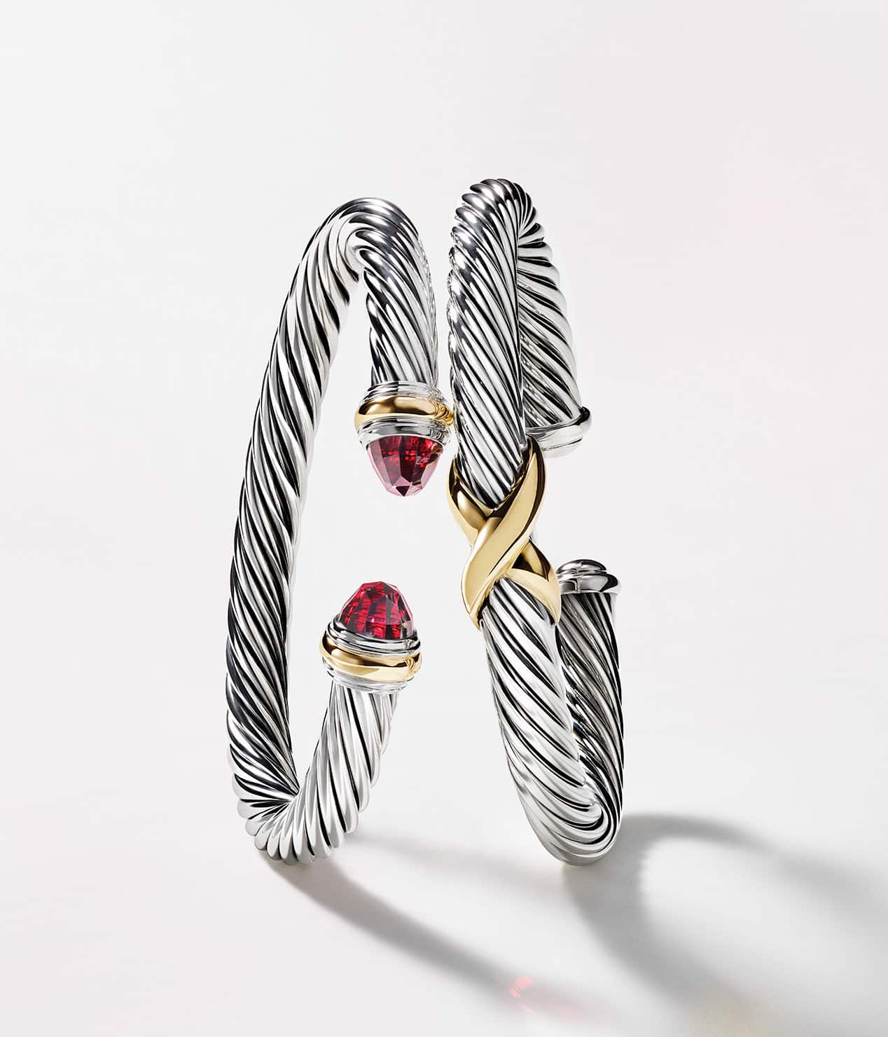 A color photograph shows two David Yurman Cable bracelets balancing against each other in front of a white background. The women's jewelry is crafted from sterling silver with 14K yellow gold accents.