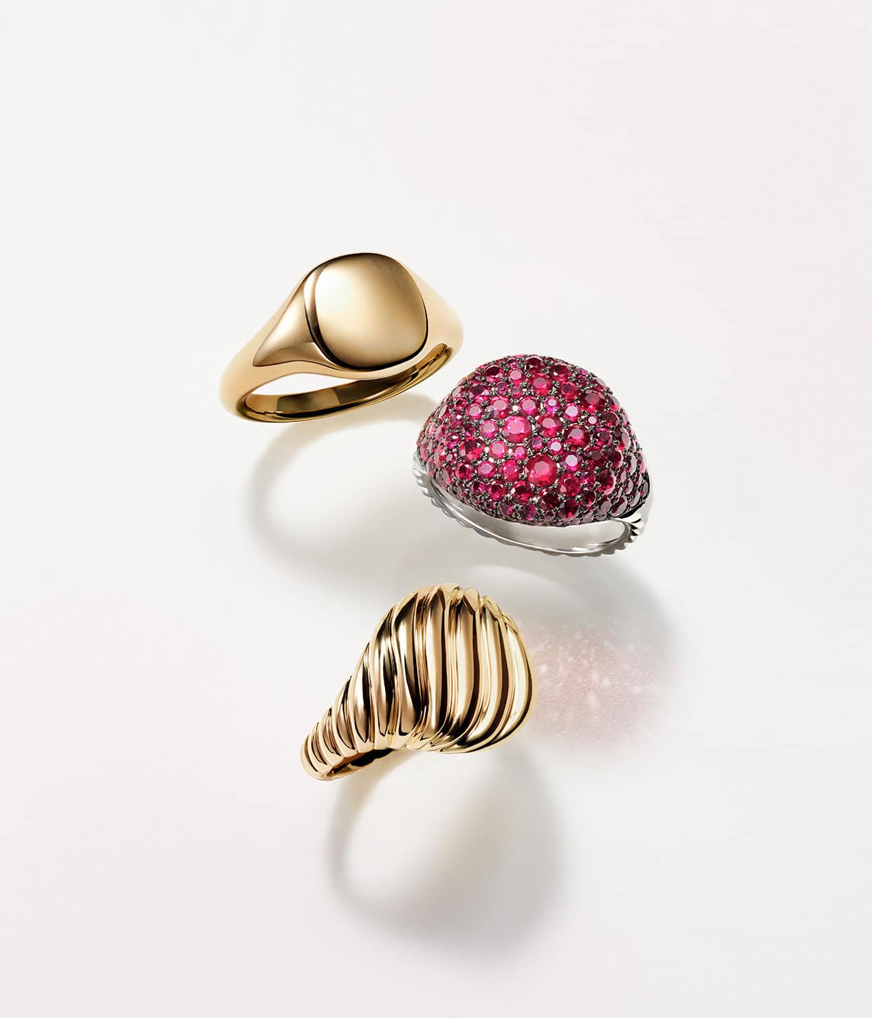 A color photograph shows three David Yurman pinky rings placed atop a white background with soft shadows. Two rings are crafted from smooth or Cabled 18K yellow gold. The final ring is crafted from 18K white gold with pavé rubies.