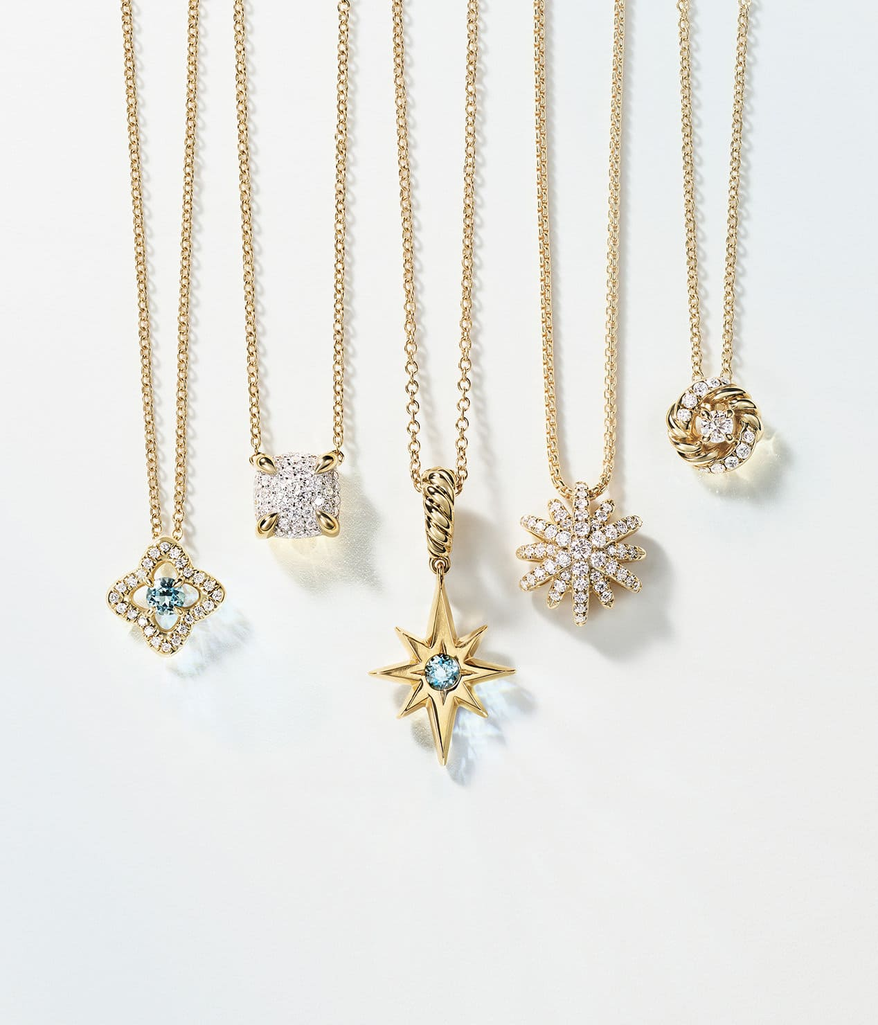 A color photograph shows a horizontal row of five David Yurman charm necklaces hanging in front of a white background. The women's jewelry is crafted from 18K yellow gold with or without pavé diamonds and aquamarine center stones. The pendants come in various shapes such as a star, circle, cushion and quatrefoil.