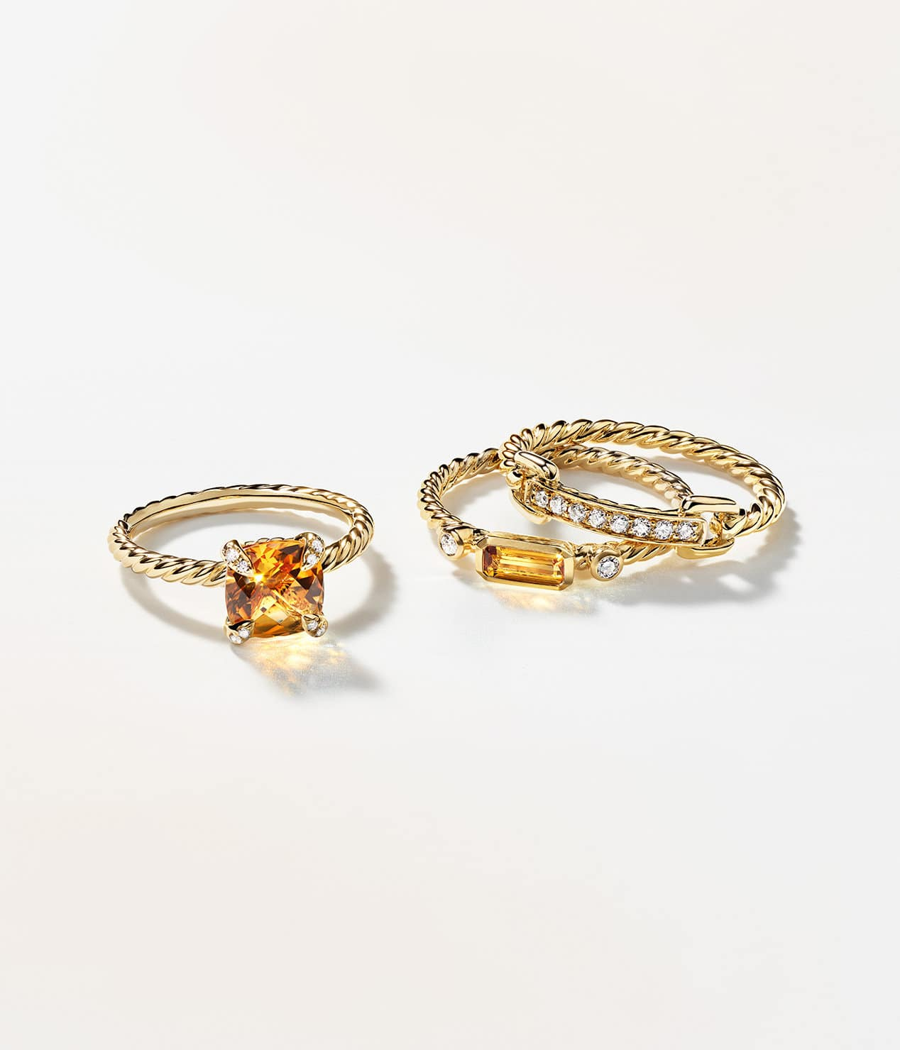 A color photograph shows three David Yurman rings scattered in two stacks on a white background with soft shadows. The women's jewelry is crafted from 18K yellow gold with pavé diamonds. Two rings feature cushion- or emerald-cut citrine center stones.