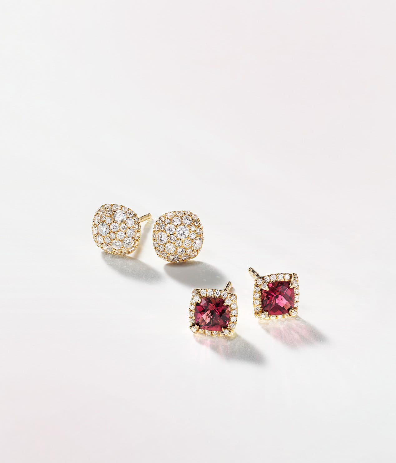 A  color photograph shows three pairs of David Yurman stud earrings scattered atop a white background with soft shadows. The women's jewelry is crafted from 18K yellow gold with pavé diamonds in the shape of circles, cushions or stars. The center pair features cushion-cut pink tourmaline center stones.