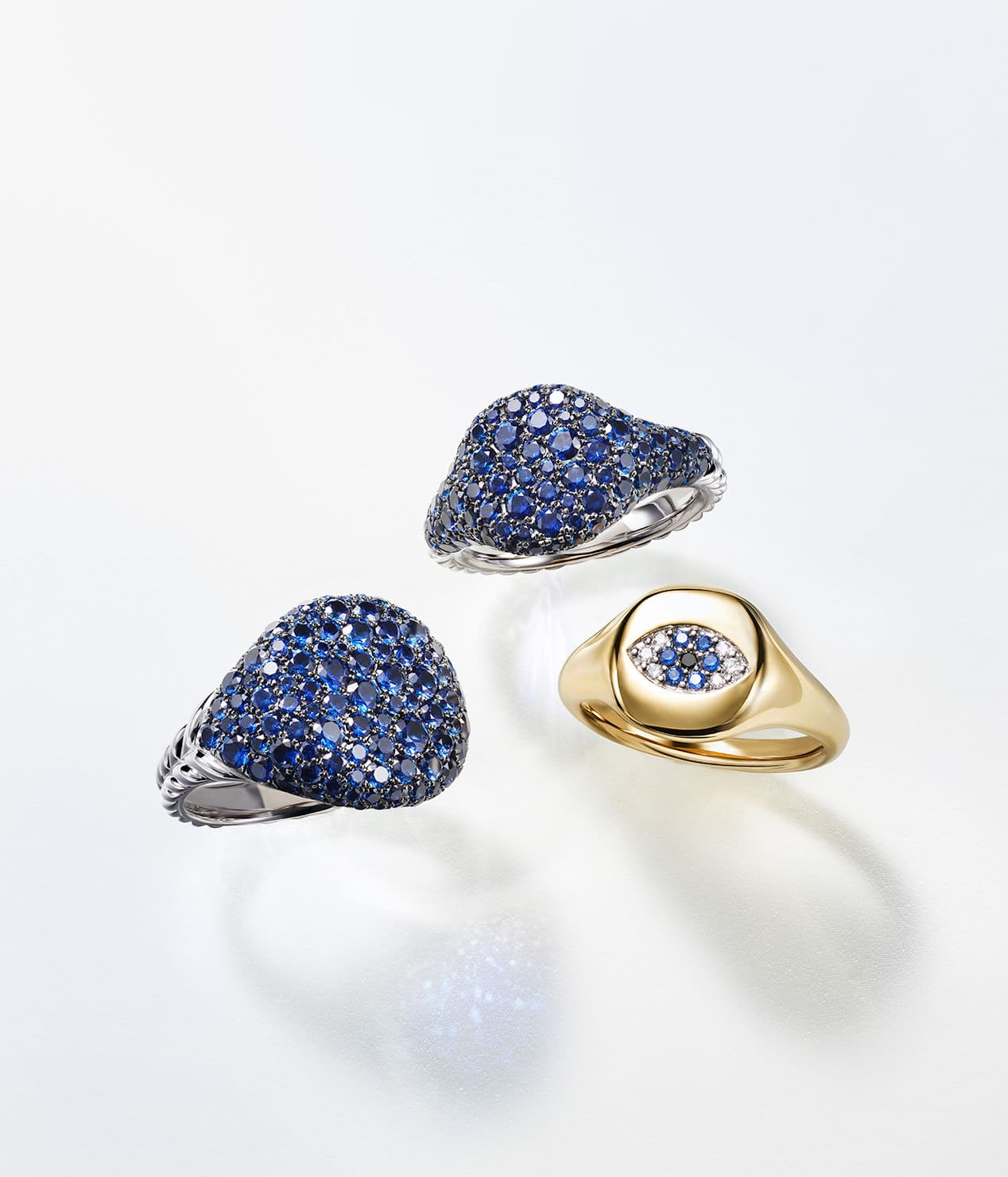A color photograph shows three David Yurman pinky rings placed atop a white background with soft shadows. Two rings are crafted from 18K white gold with pavé blue sapphires. The final ring is crafted from 18K yellow gold with pavé diamonds and blue sapphires set to look like an evil eye.