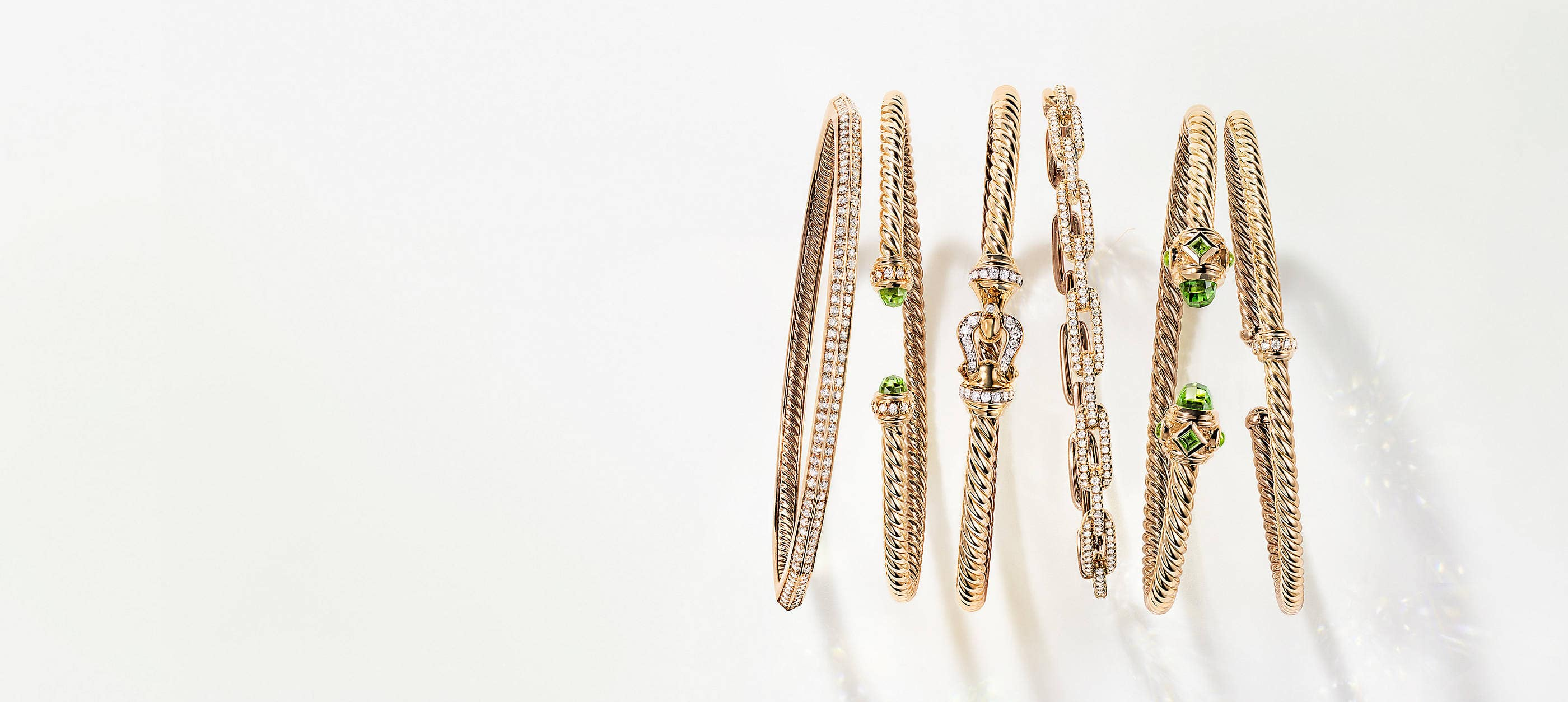 A horizontal row of six David Yurman Cable, chain and faceted bracelets standing on a white background with soft shadows. The women's jewelry is crafted from 18K yellow gold with or without pavé diamonds and peridot accents on the bracelet ends.