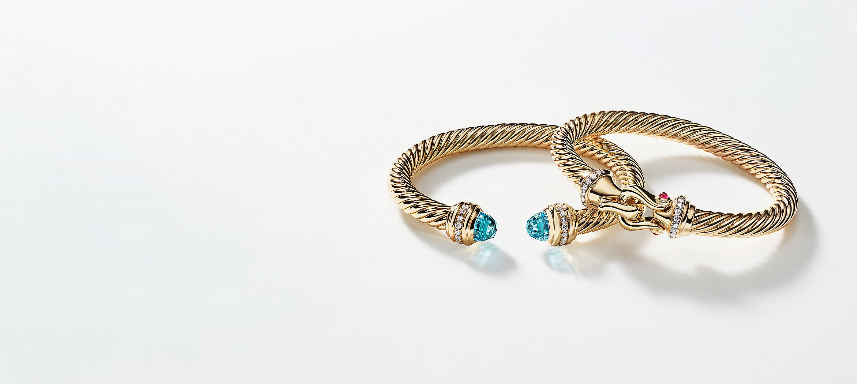 Two David Yurman Cable bracelets slightly overlapped atop a white background with soft shadows. The women's jewelry is crafted from 18K yellow gold with pavé diamonds. The bracelet on the left features blue topazes at the ends while the other bracelet is accented with rubies near its center buckle.