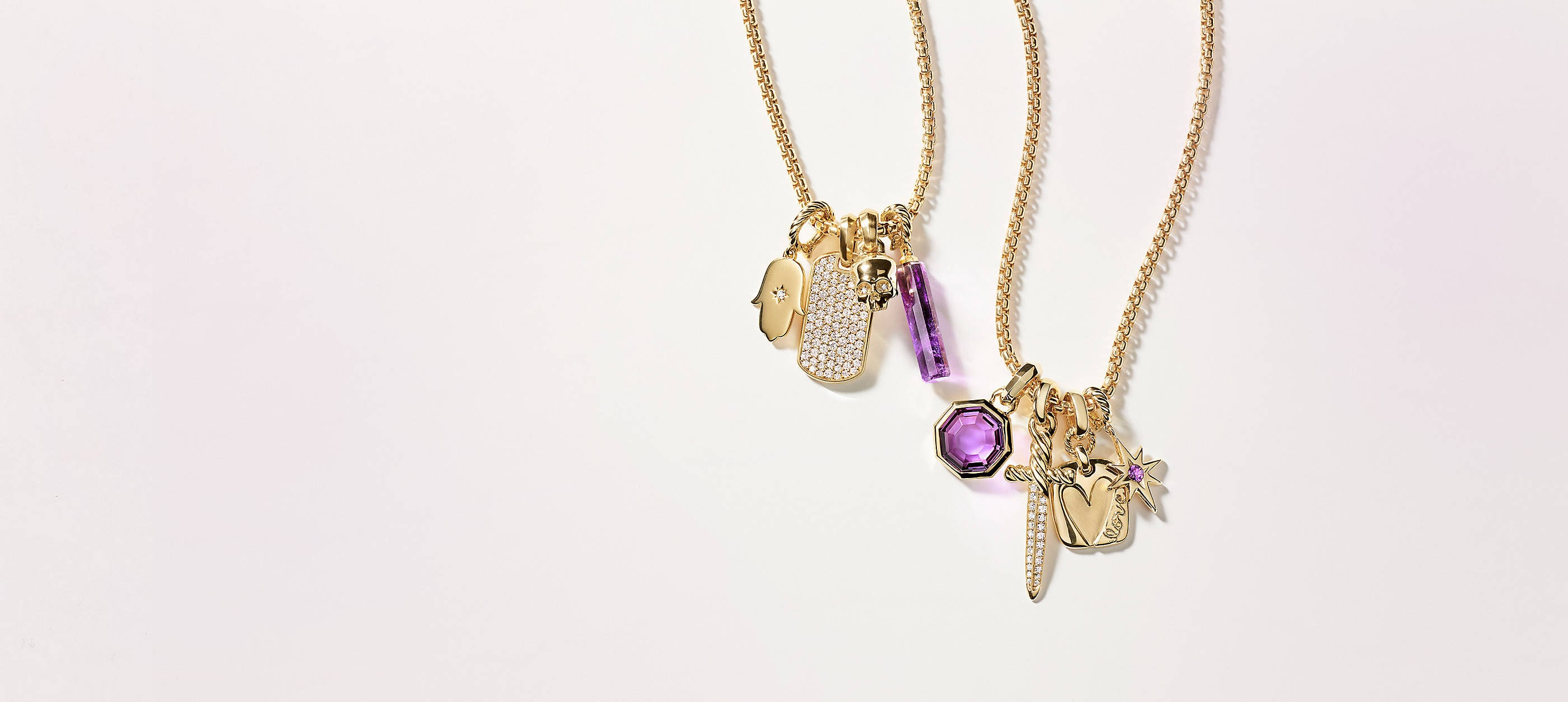 Two David Yurman chain necklaces strung with four amulets each draped on a white background. The women's jewelry is crafted from 18K yellow gold with or without pavé diamonds and amethyst center stones. The amulets come in various shapes such as a Hamsa hand, tag, skull, barrel, octagon, dagger and heart.