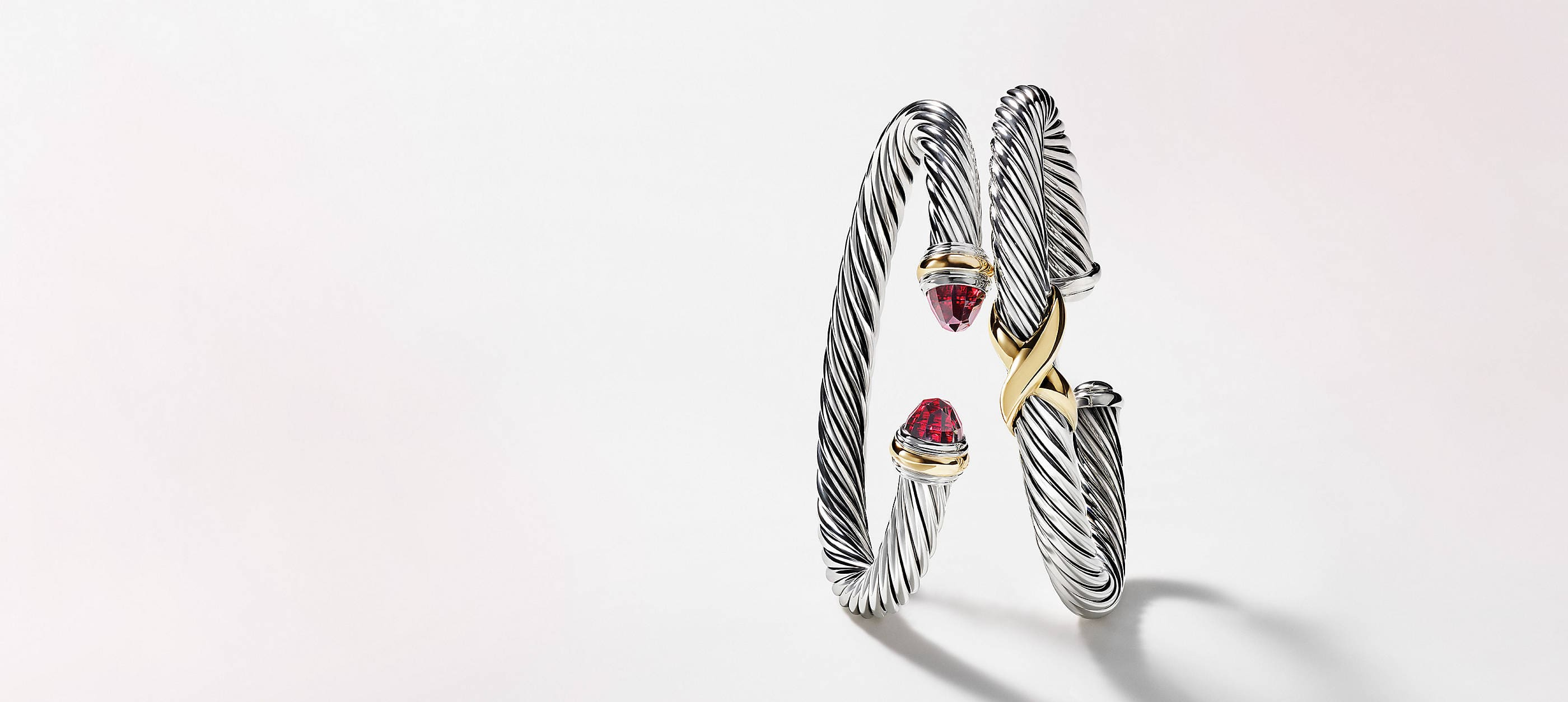 Two David Yurman Cable bracelets balancing against each other in front of a white background. The women's jewelry is crafted from sterling silver with 14K yellow gold accents.