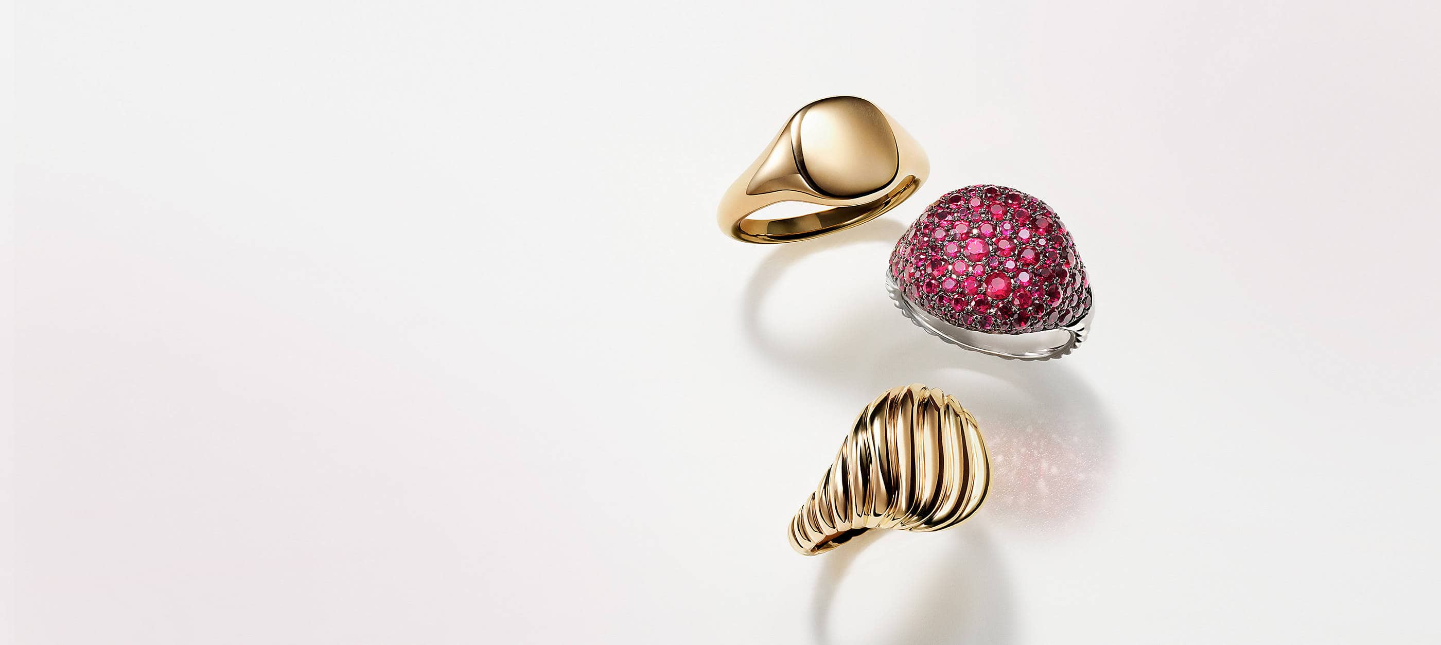 Three David Yurman pinky rings placed atop a white background with soft shadows. Two rings are crafted from smooth or Cabled 18K yellow gold. The final ring is crafted from 18K white gold with pavé rubies.