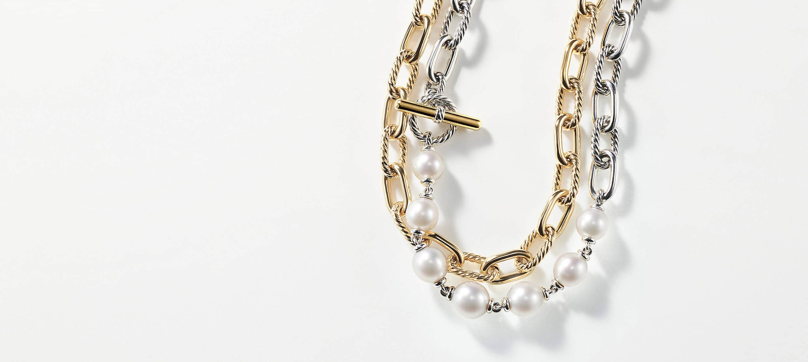 Two David Yurman chain necklaces overlapped atop a white background with soft shadows from the jewelry. The women's jewelry is crafted from 18K yellow gold or sterling silver with an 18K yellow gold toggle. The mixed metal necklace features cultured pearls near the center.