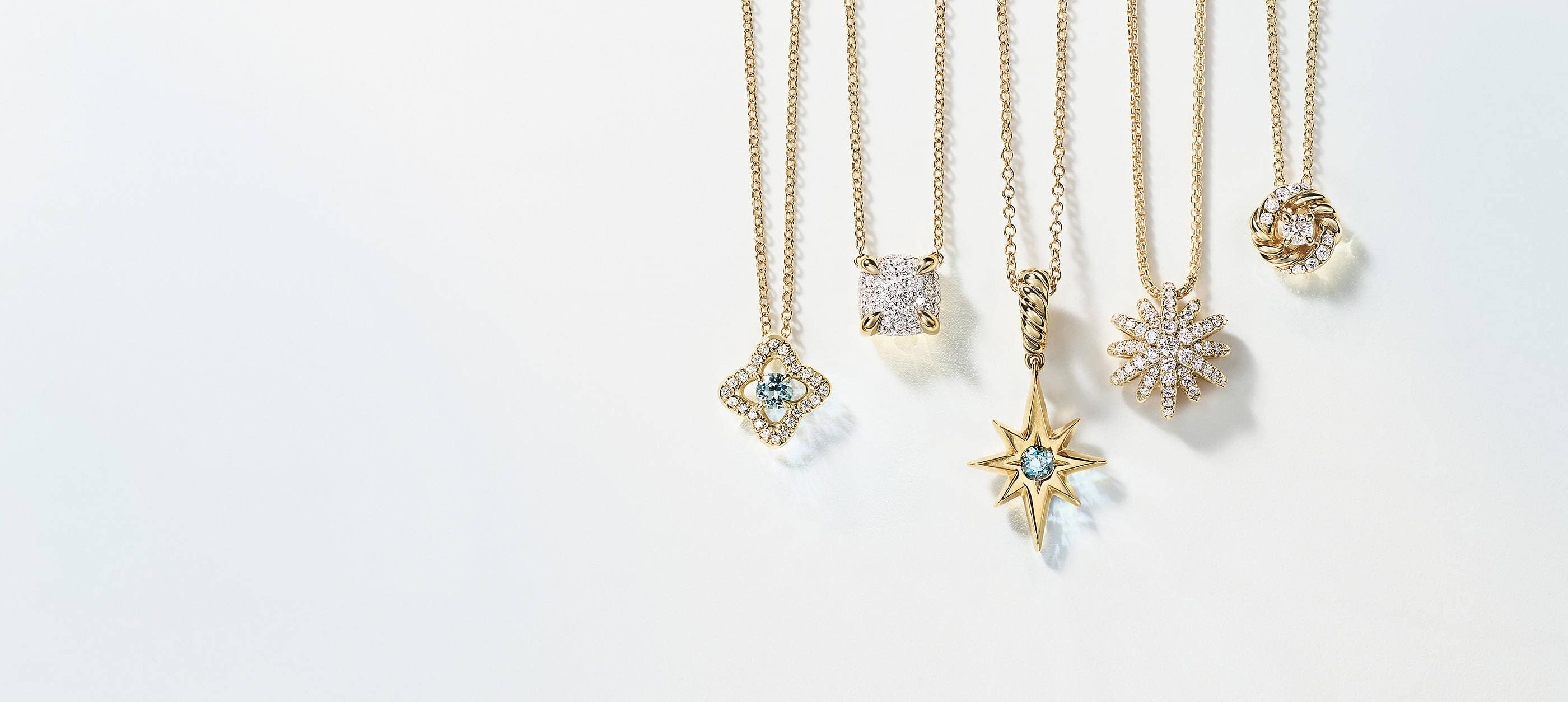 A horizontal row of five David Yurman charm necklaces hanging in front of a light blue and white background. The women's jewelry is crafted from 18K yellow gold with or without pavé diamonds and aquamarine center stones. The pendants come in various shapes such as a star, circle, cushion and quatrefoil.