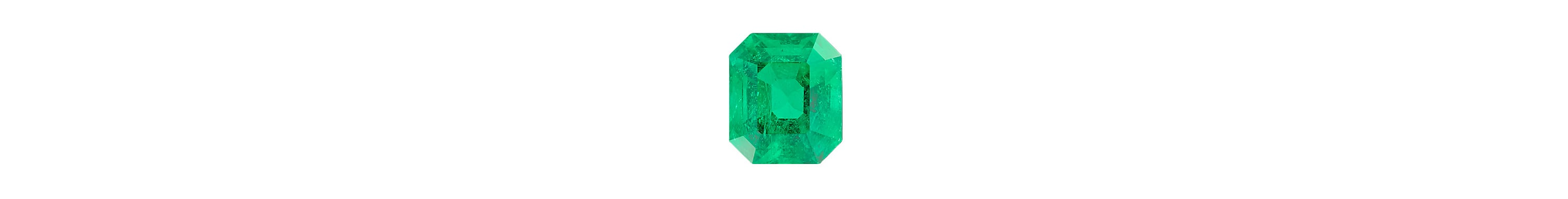 A color photograph shows a close-up shot of a large cushion-cut emerald on a black background.