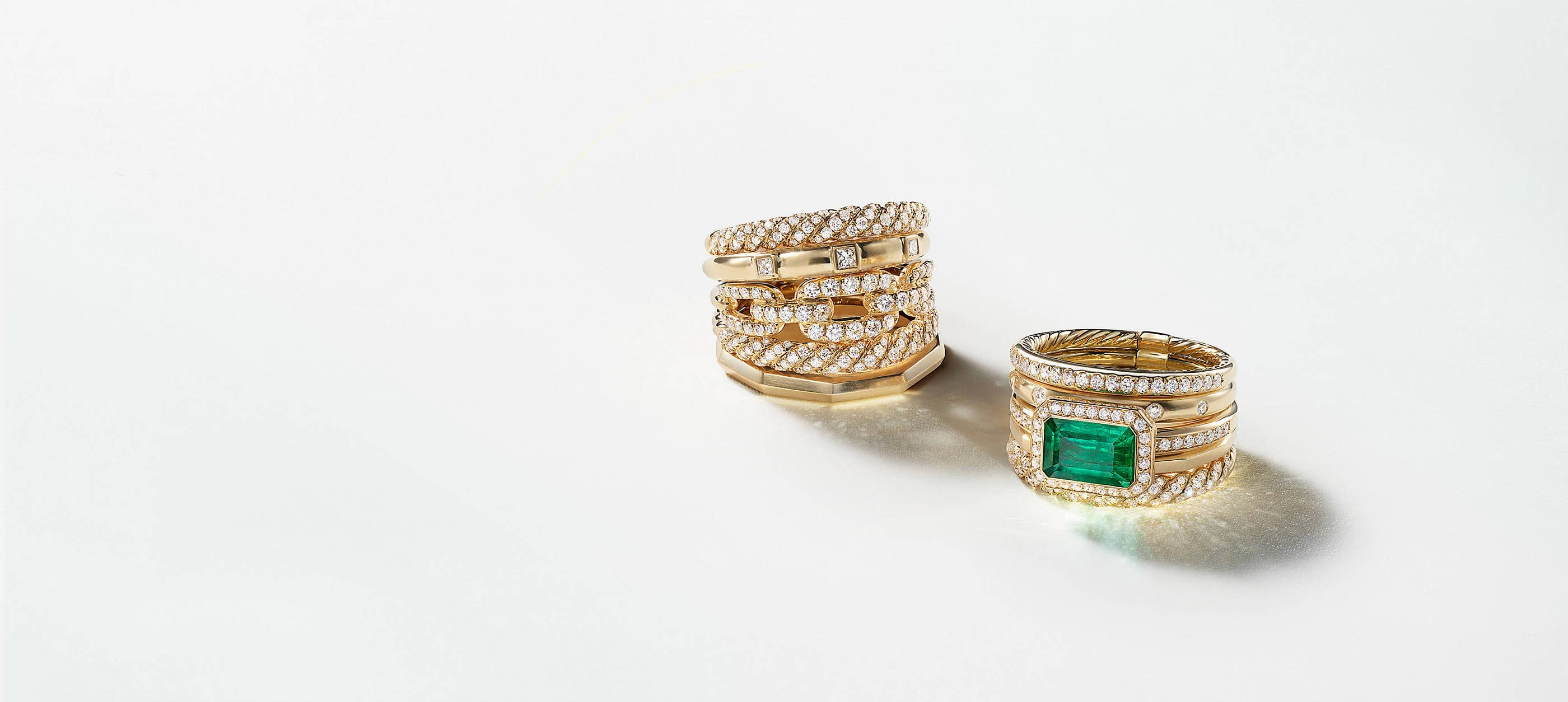 A color photograph shows two David Yurman Stax multi-row rings placed on a white background with soft shadows and reflections of light from the jewelry. The women's jewelry is crafted from 18K yellow gold with pavé diamonds. The ring on the right features an emerald center stone.
