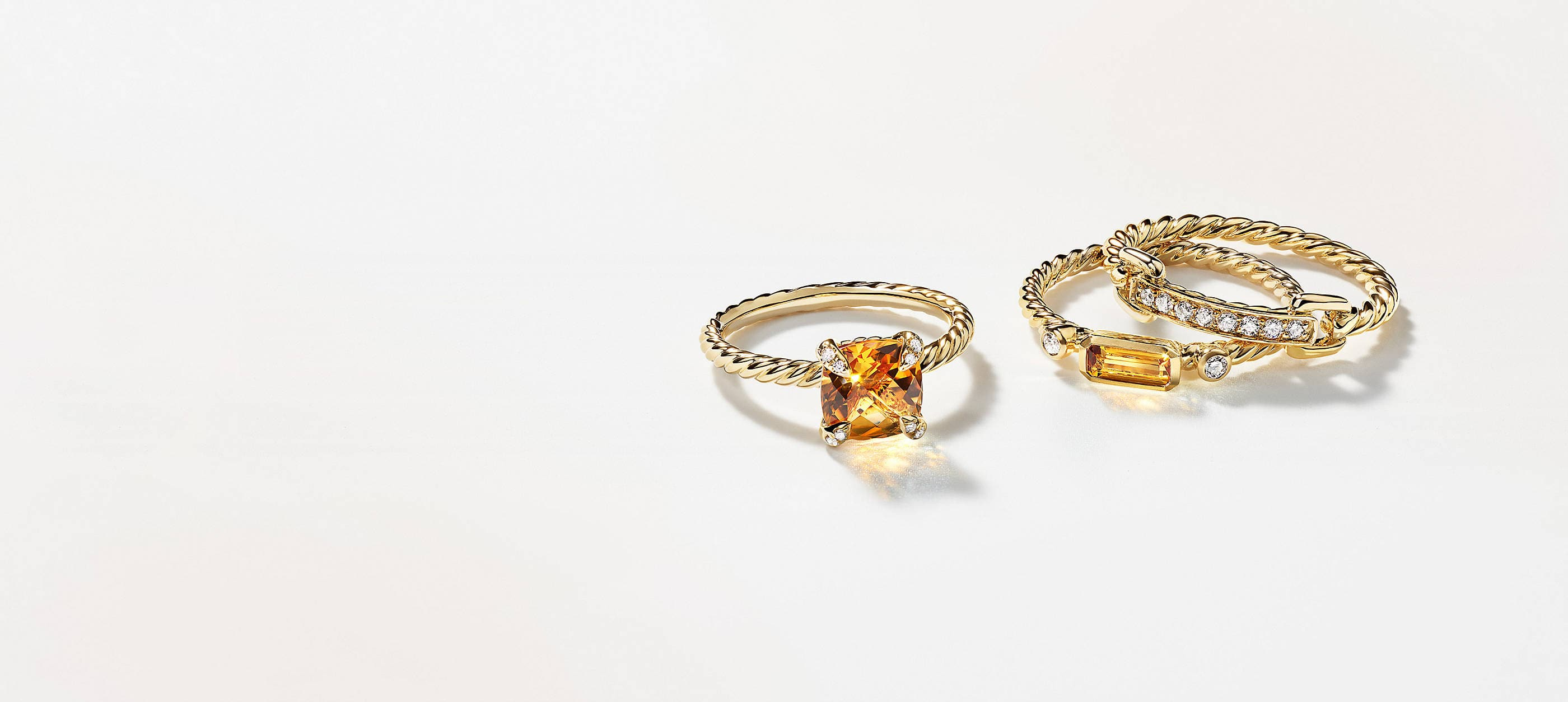 Three David Yurman rings scattered in two stacks on a white background with soft shadows. The women's jewelry is crafted from 18K yellow gold with pavé diamonds. Two rings feature cushion- or emerald-cut citrine center stones.