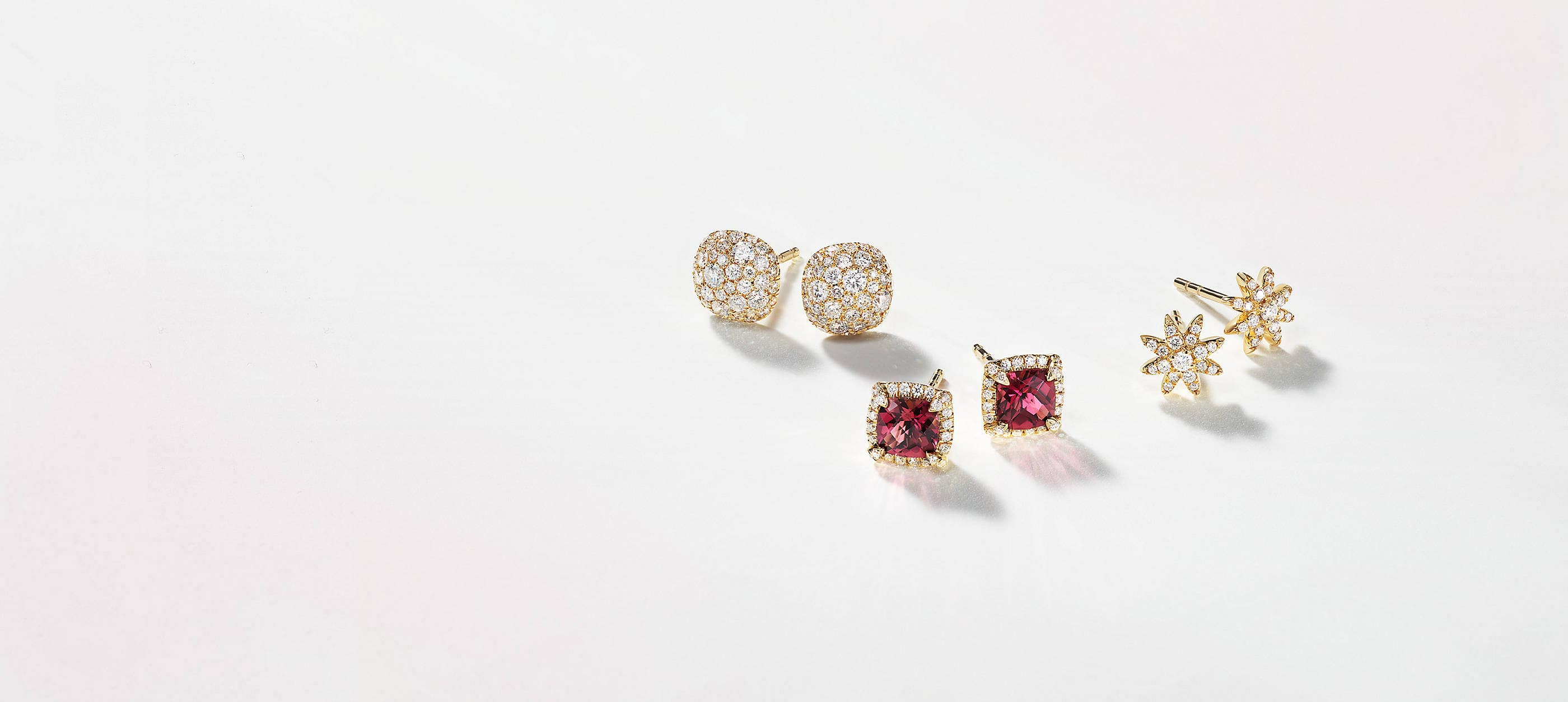 Three pairs of David Yurman stud earrings scattered atop a white background with soft shadows. The women's jewelry is crafted from 18K yellow gold with pavé diamonds in the shape of circles, cushions or stars. The center pair features cushion-cut pink tourmaline center stones.