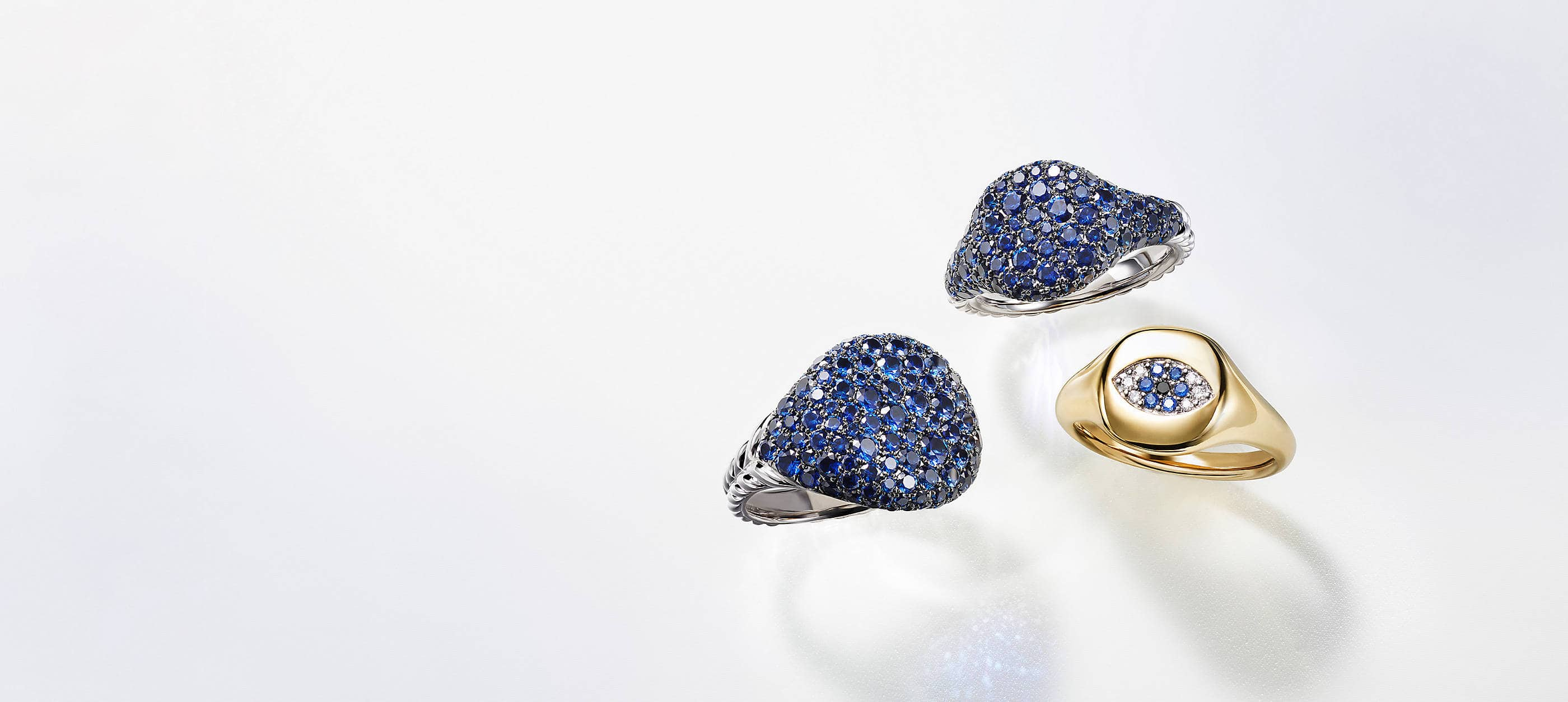 Three David Yurman pinky rings placed atop a white background with soft shadows. Two rings are crafted from 18K white gold with pavé blue sapphires. The final ring is crafted from 18K yellow gold with pavé diamonds and blue sapphires set to look like an evil eye.