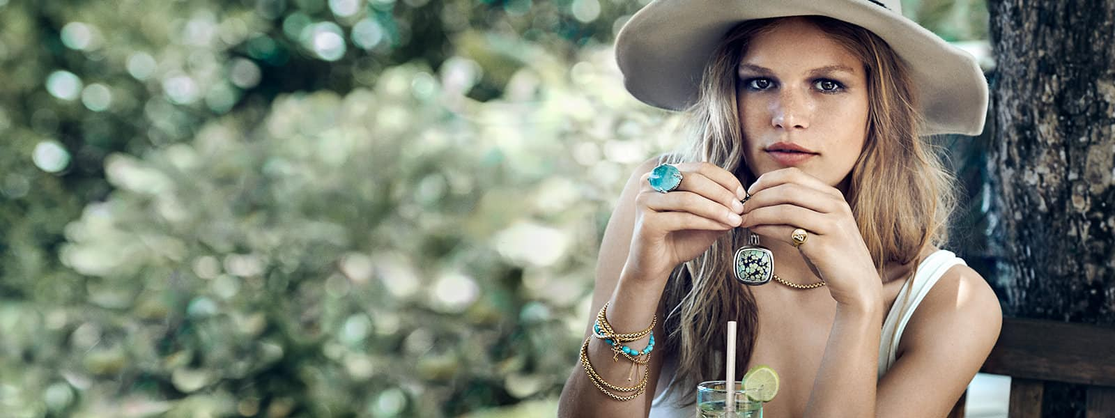 Model Anna Ewers wearing David Yurman Continuance® and Pinky Ring jewelry in sterling silver or 18K white gold with or without South Sea pearls and pavé diamonds in front of the shoreline.