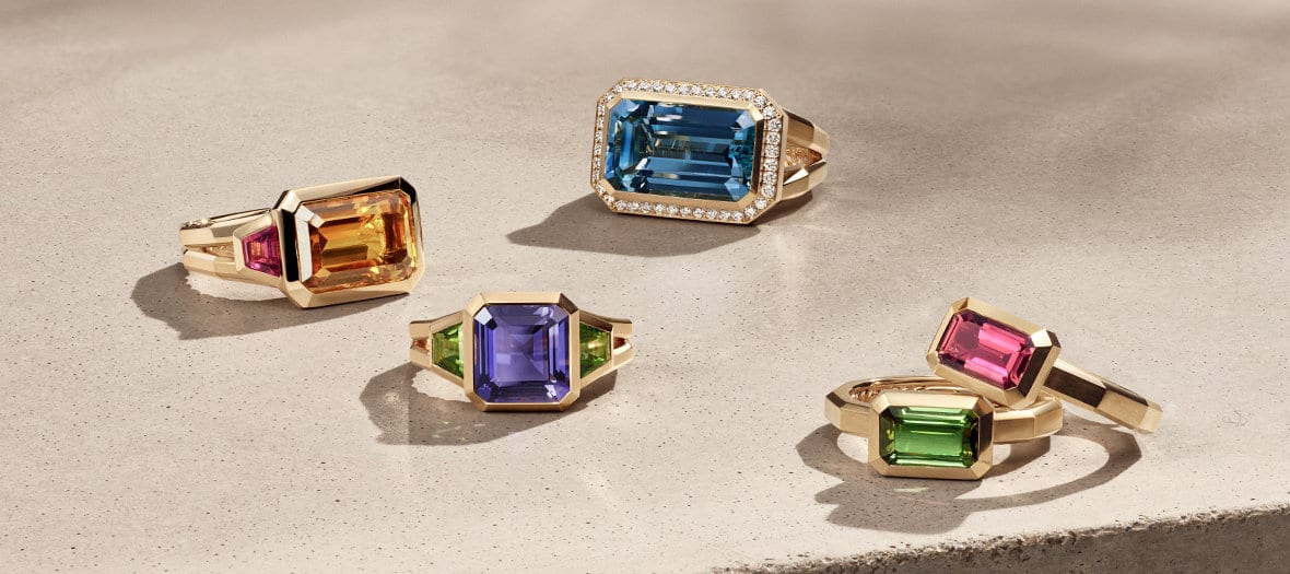 David Yurman Novella rings in 18K yellow gold with citrine and rhodalite garnet, iolite and green tourmaline, blue topaz and white diamonds, or green or pink tourmaline, arranged in a group on a sandy-colored stone illuminated with the designs casting long shadows.