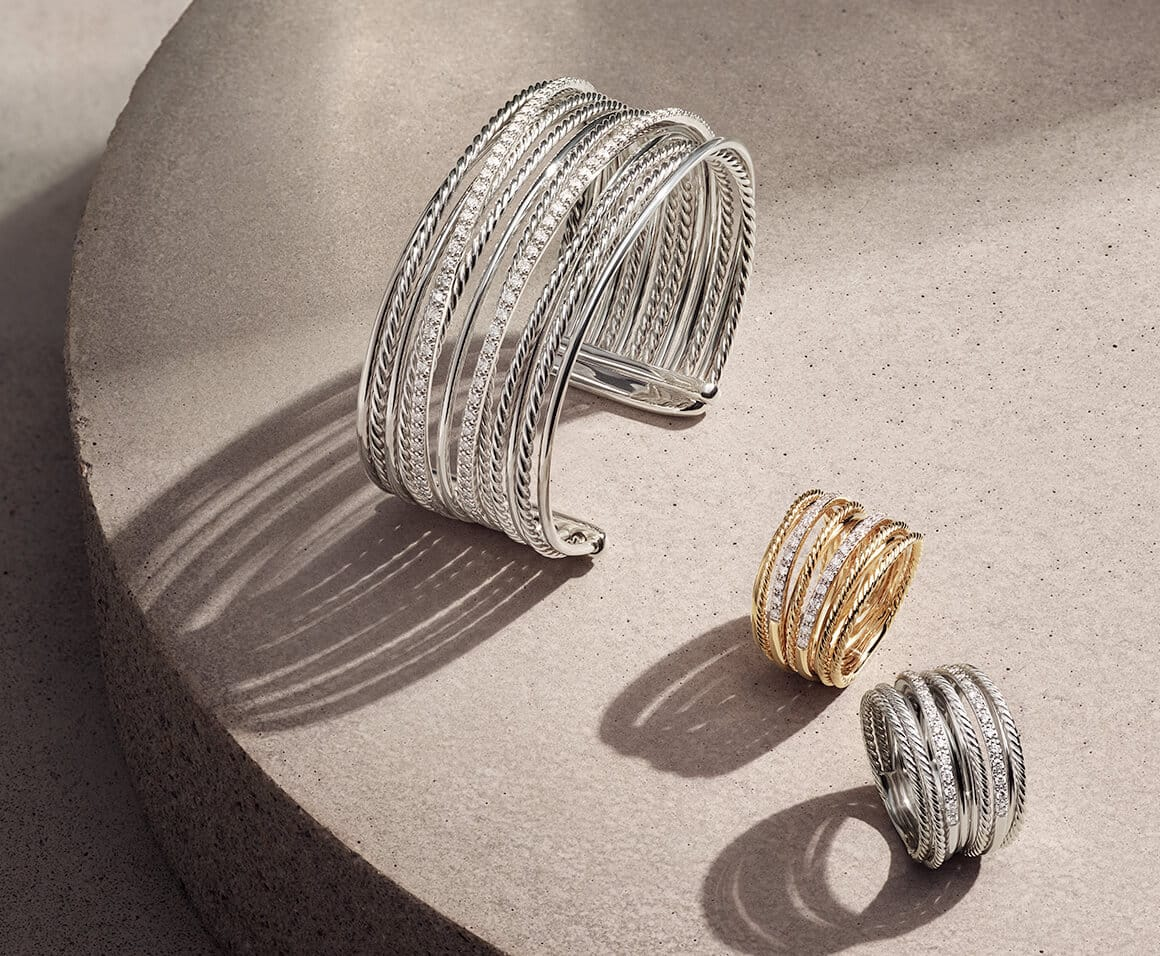 David Yurman The Crossover Collection cuff and rings in sterling silver or 18K yellow gold with white diamonds, in a group on a sandy-colored stone illuminated with the designs casting long shadows.