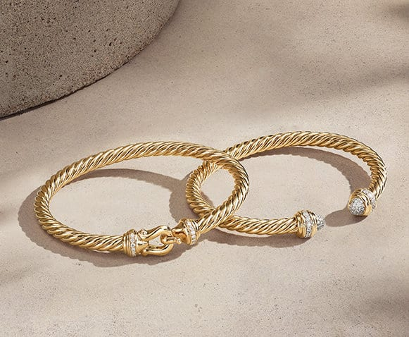 David Yurman The Cable Collection® bracelets in 18K yellow gold with pavé diamonds on a light pink textured stone with long shadows.
