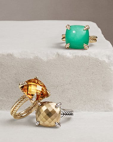 David Yurman Chatelaine rings in 18K yellow gold or sterling silver with white diamonds and citrine, bonded 18K yellow gold dome or chrysoprase, arranged across two levels of a white, textured stone.