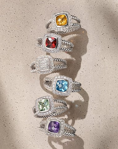 David Yurman Petite Albion rings in sterling silver with white diamonds and citrine, garnet, blue topaz, prasiolite or amethyst, arranged in a vertical stack on a sandy-colored stone illuminated with the designs casting long shadows.
