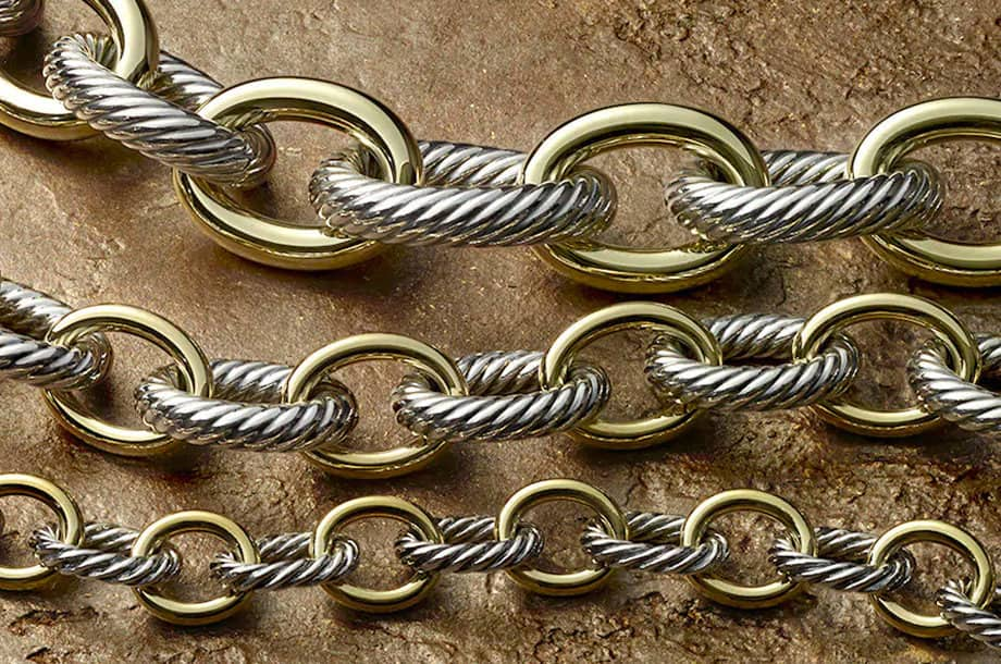 A close-up of David Yurman oval-chain necklaces that juxtapose Cable links in sterling silver with smooth 18K yellow gold links.